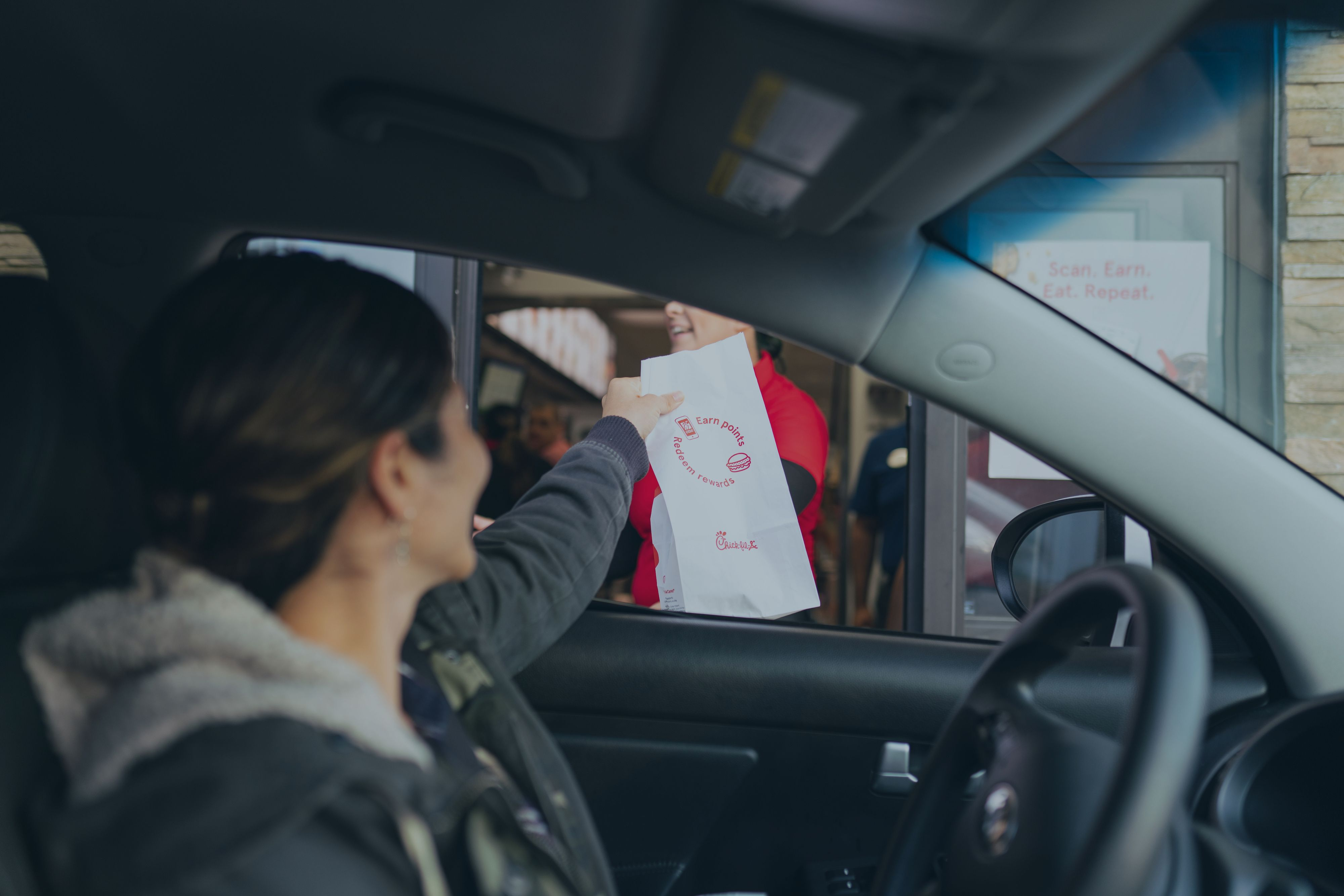 A woman at a Chik-fil-a drivethrough accepting a bag from the attednant