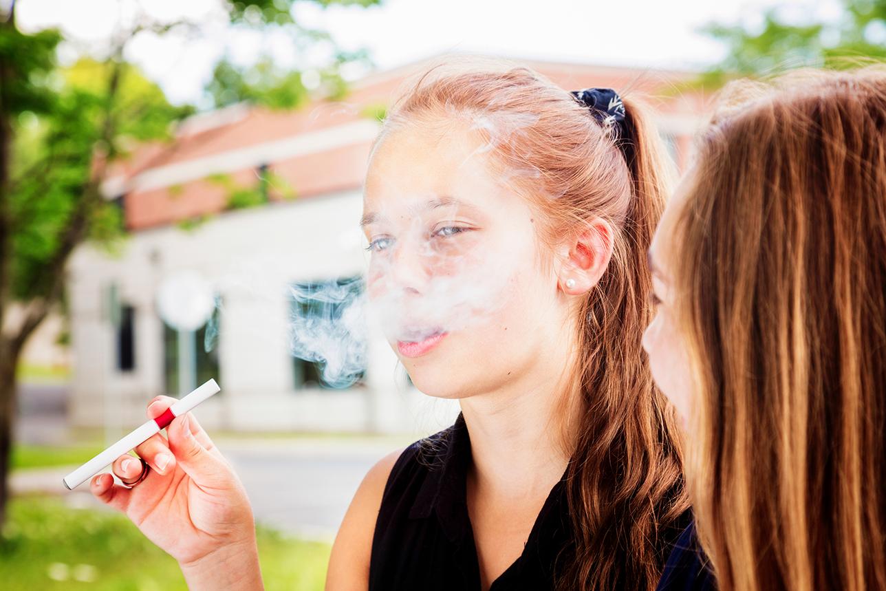 Una jóven adolescente fumando un cigarrillo electrónico