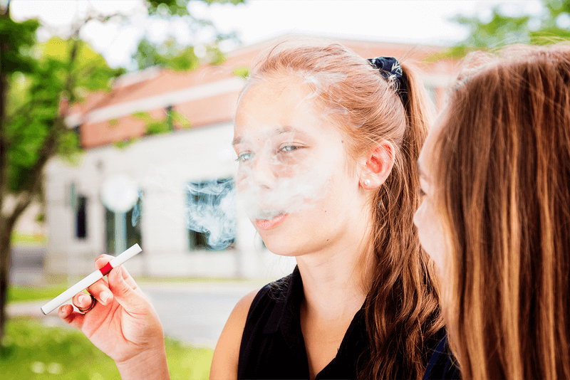 A young teen smoking an e-cigarrette