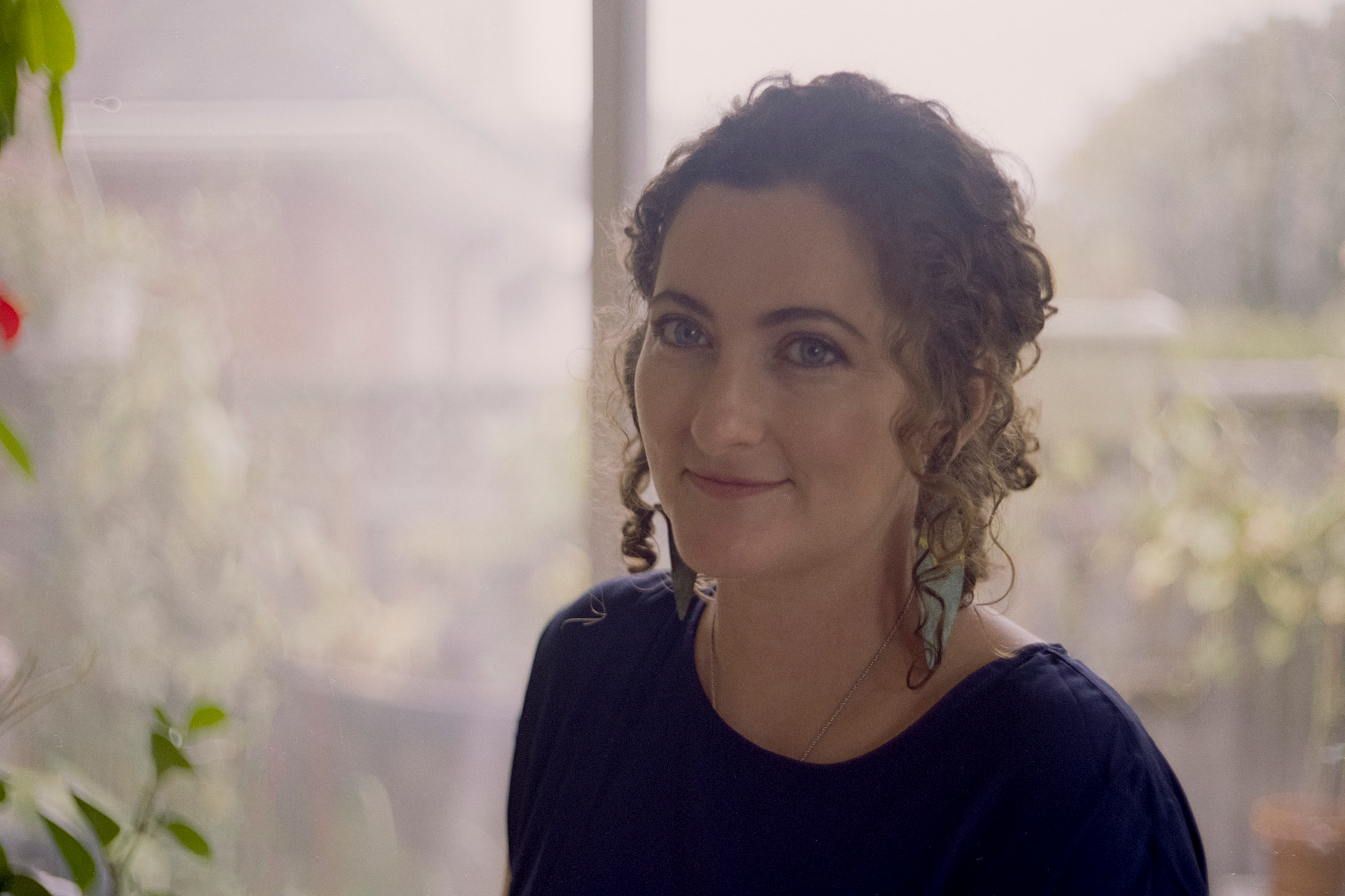 curlied hair woman standing near window