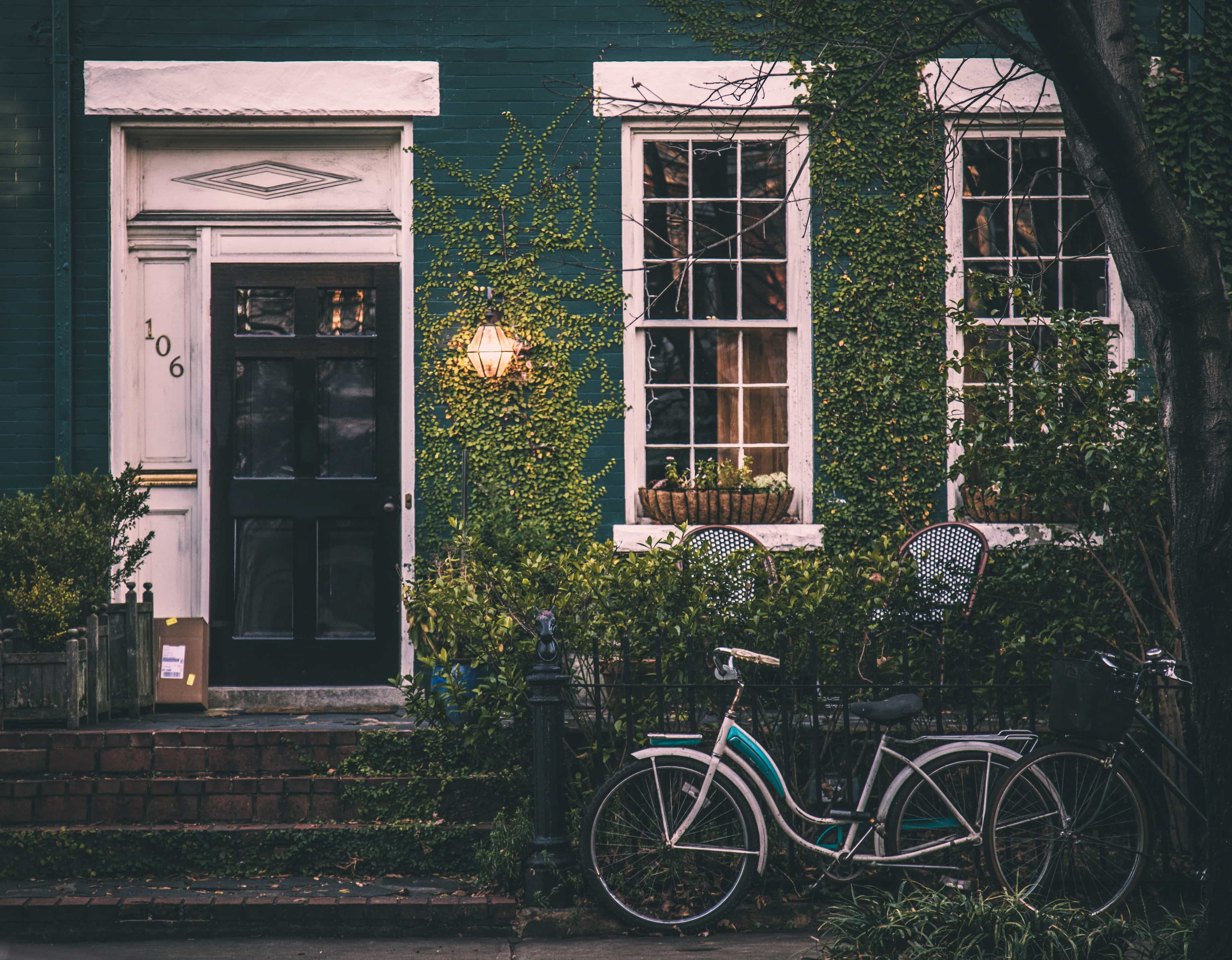 Small house exterior with shrubberies and bicycle