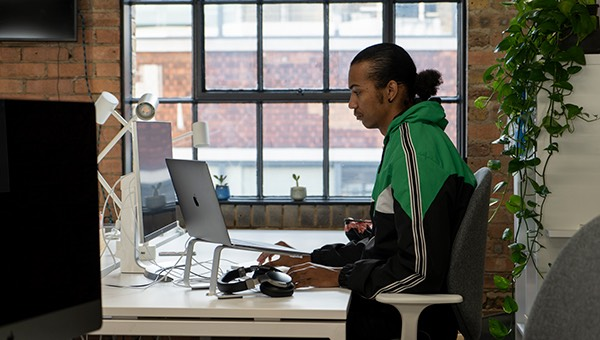 Aaron sitting at his desk and working