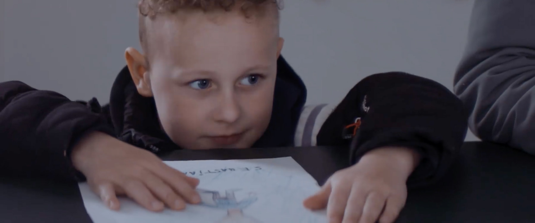 A boy with a drawing in the DSAM campaign film