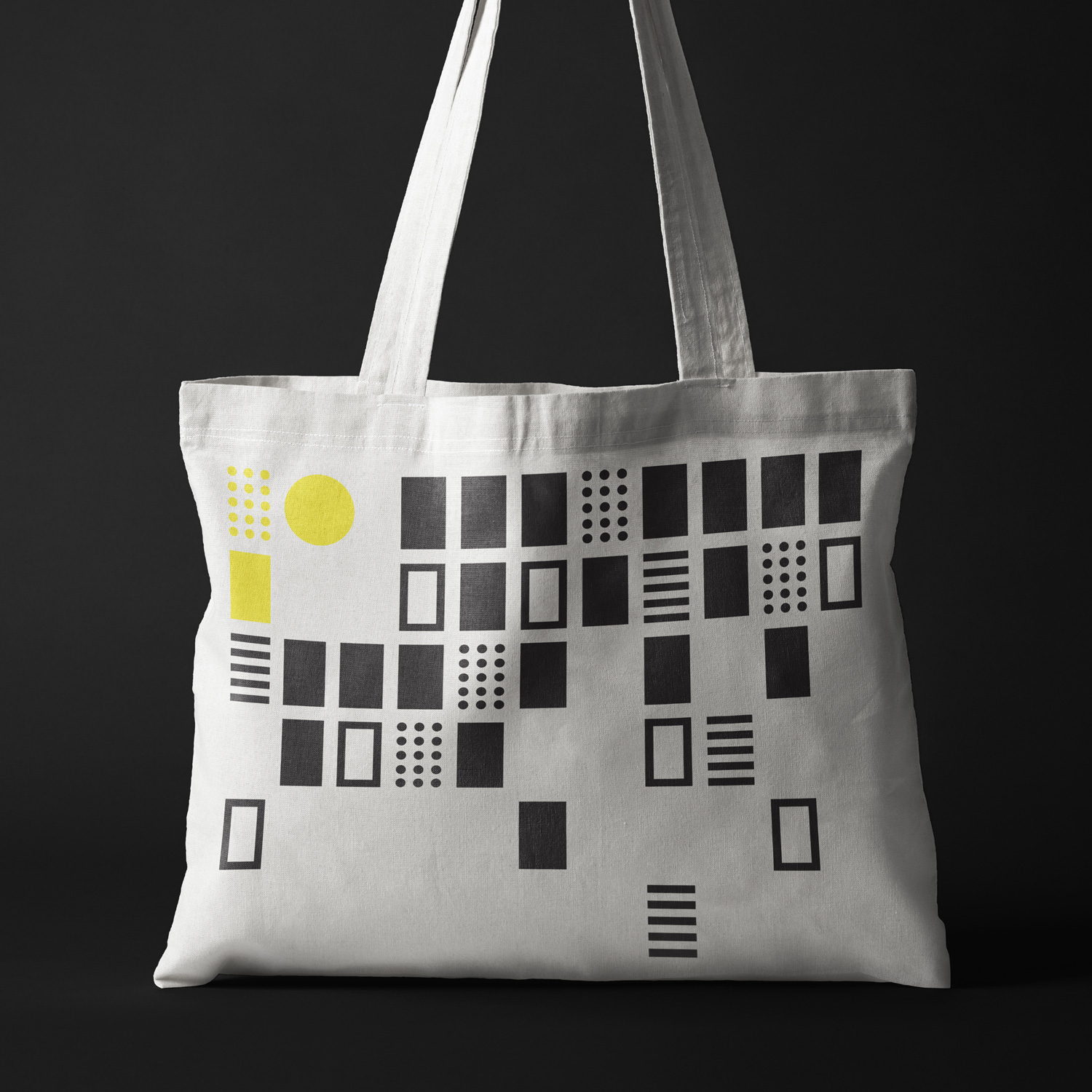 The visual identity of Rumsans with graphic elements in the colors black, white and yellow. A white tote bag with the graphic elements printed on it.