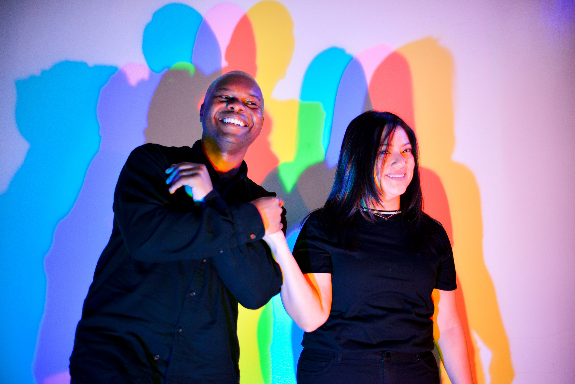 A man and woman with multi-colored shadows cast on the wall behind them.