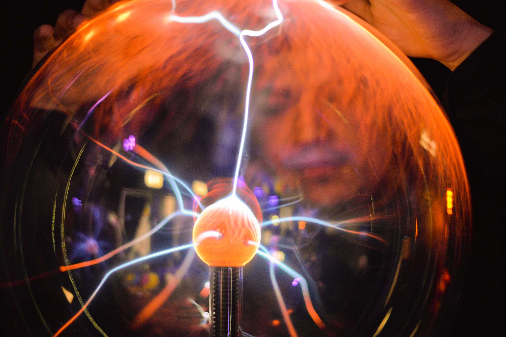 Person looking into a plasma globe.