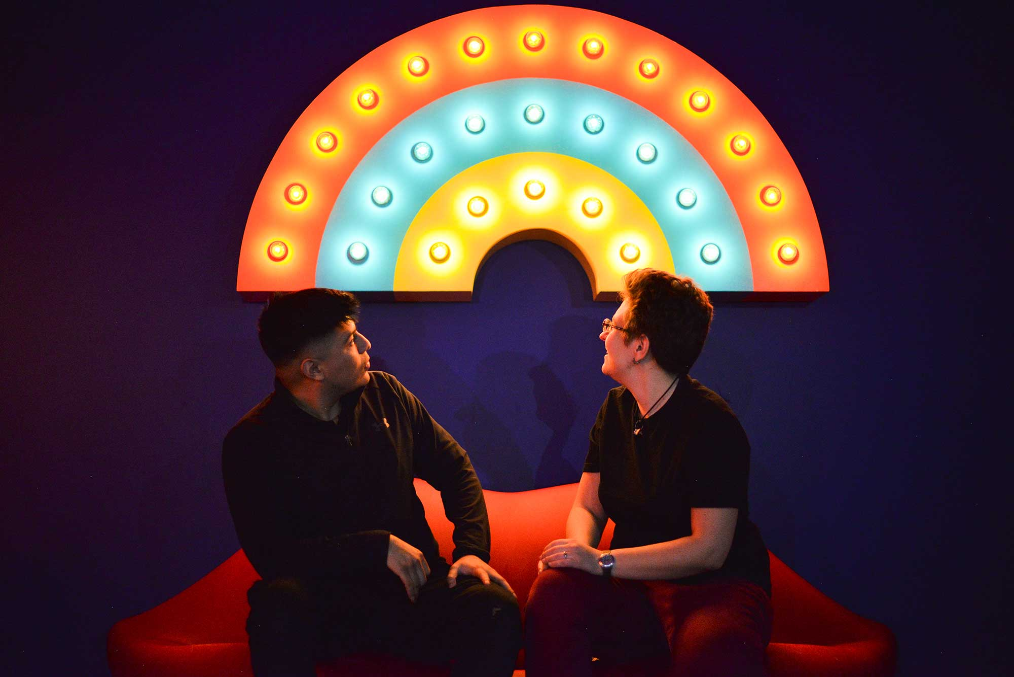Two people seated in front of a rainbow made of lightbulbs.