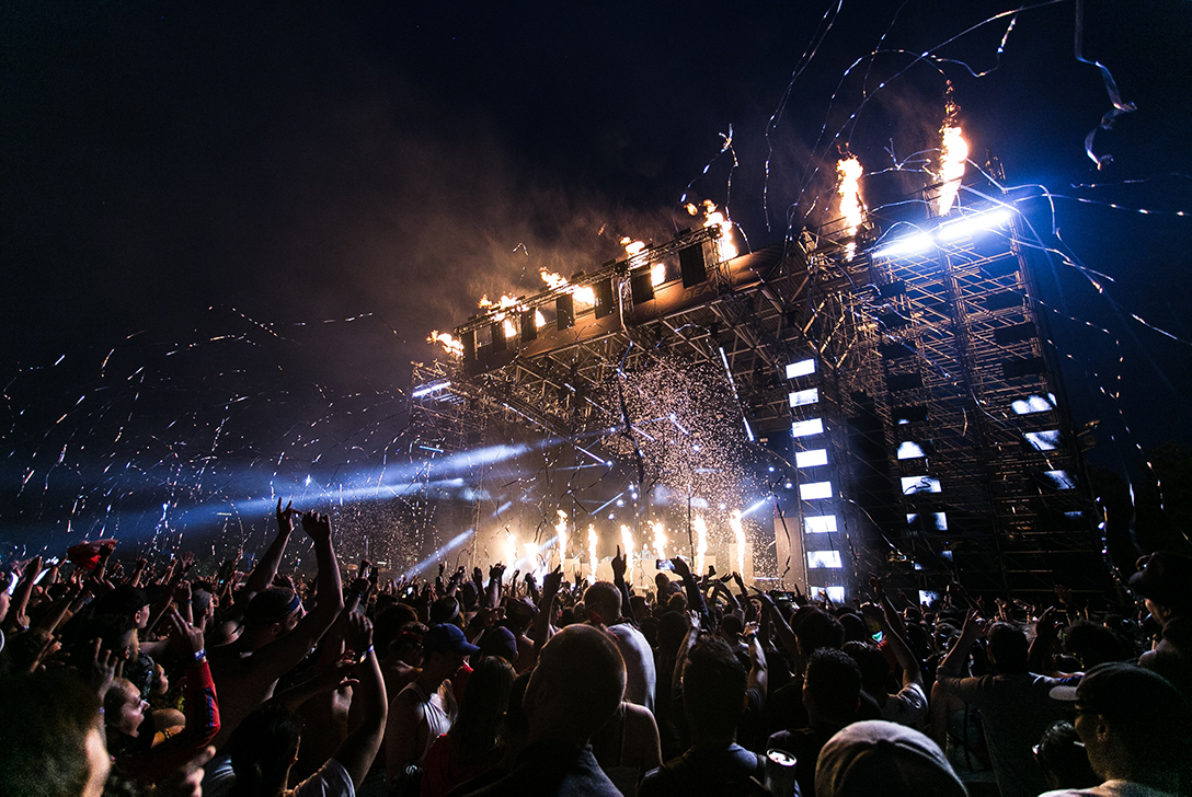 An image of a concert or a festival at night with a large crowd