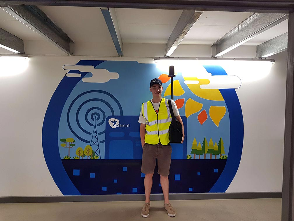 A photo of a staff member ready to test network experience in front of a Metricell mural.