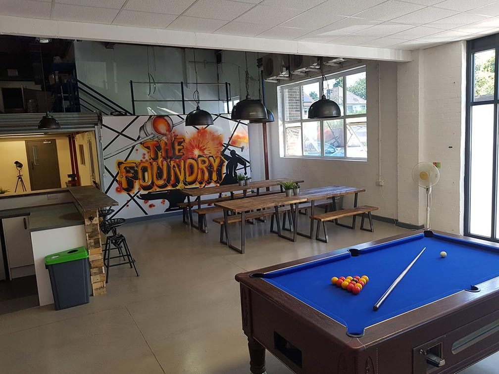 A photo of the Foundry showing a pool table and picnic benches