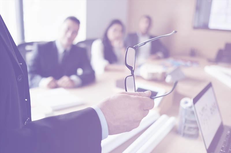 Photo of a man delivering a presentation in a boardroom
