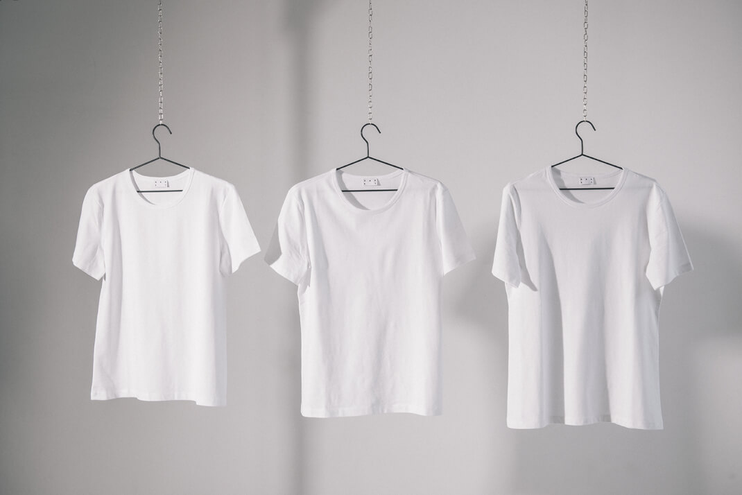Three white Asket Tee Shirts hanging up to show varying lengths available