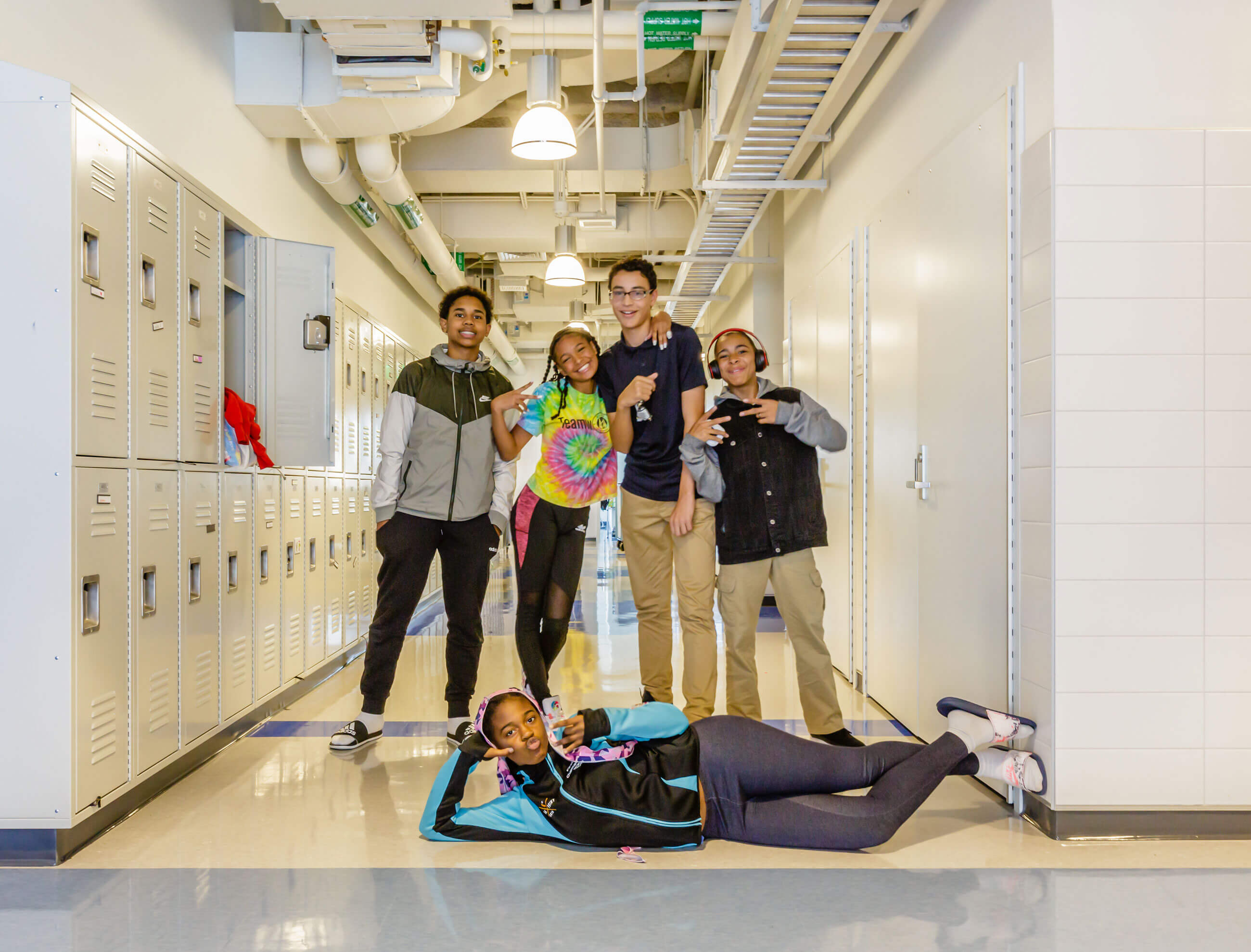 Students posing in a hallway with open lockers and exposed mechanical systems in the ceiling.