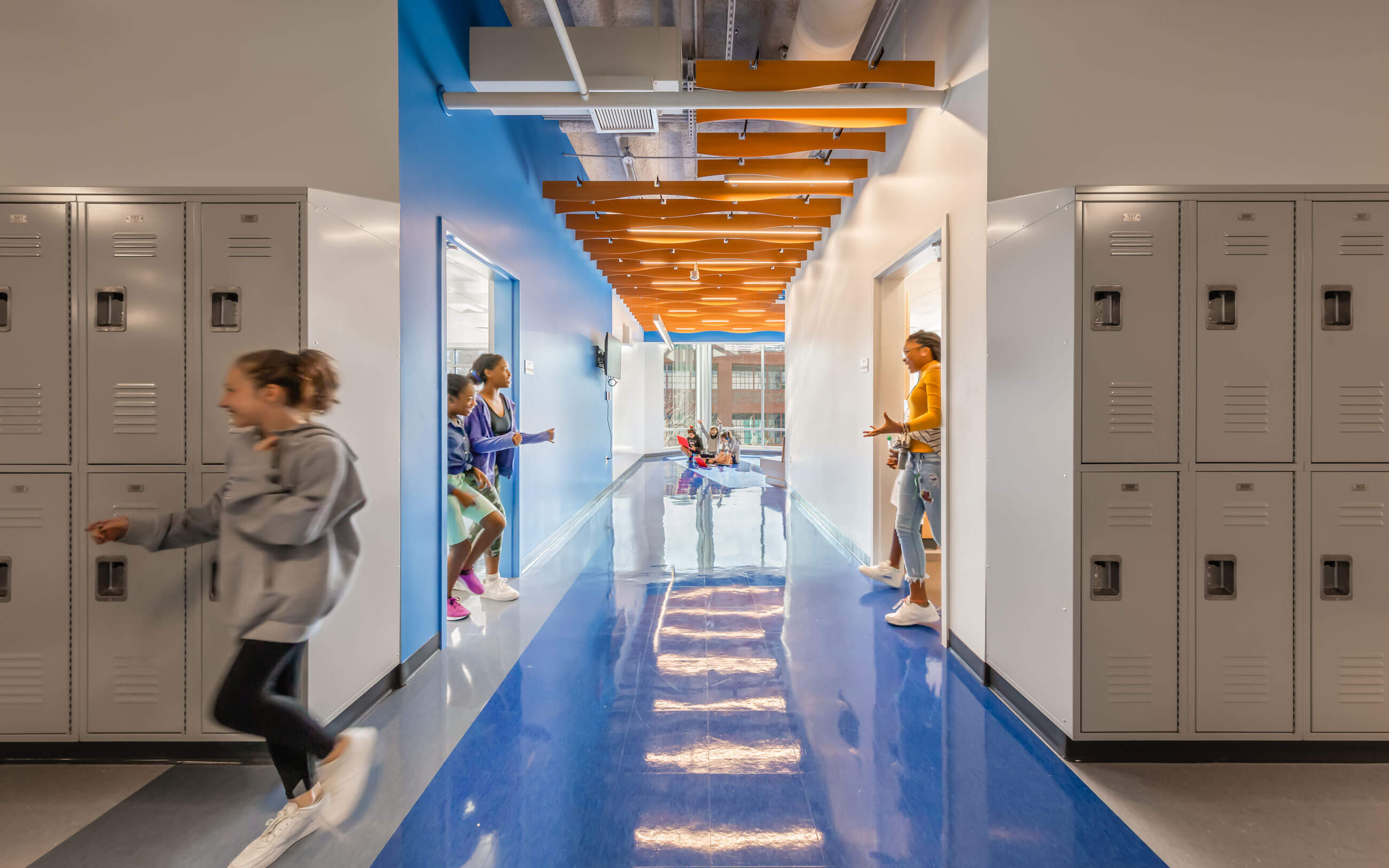 Students coming out of the classroom into a blue hallway with gray lockers and wavy ceiling panels.