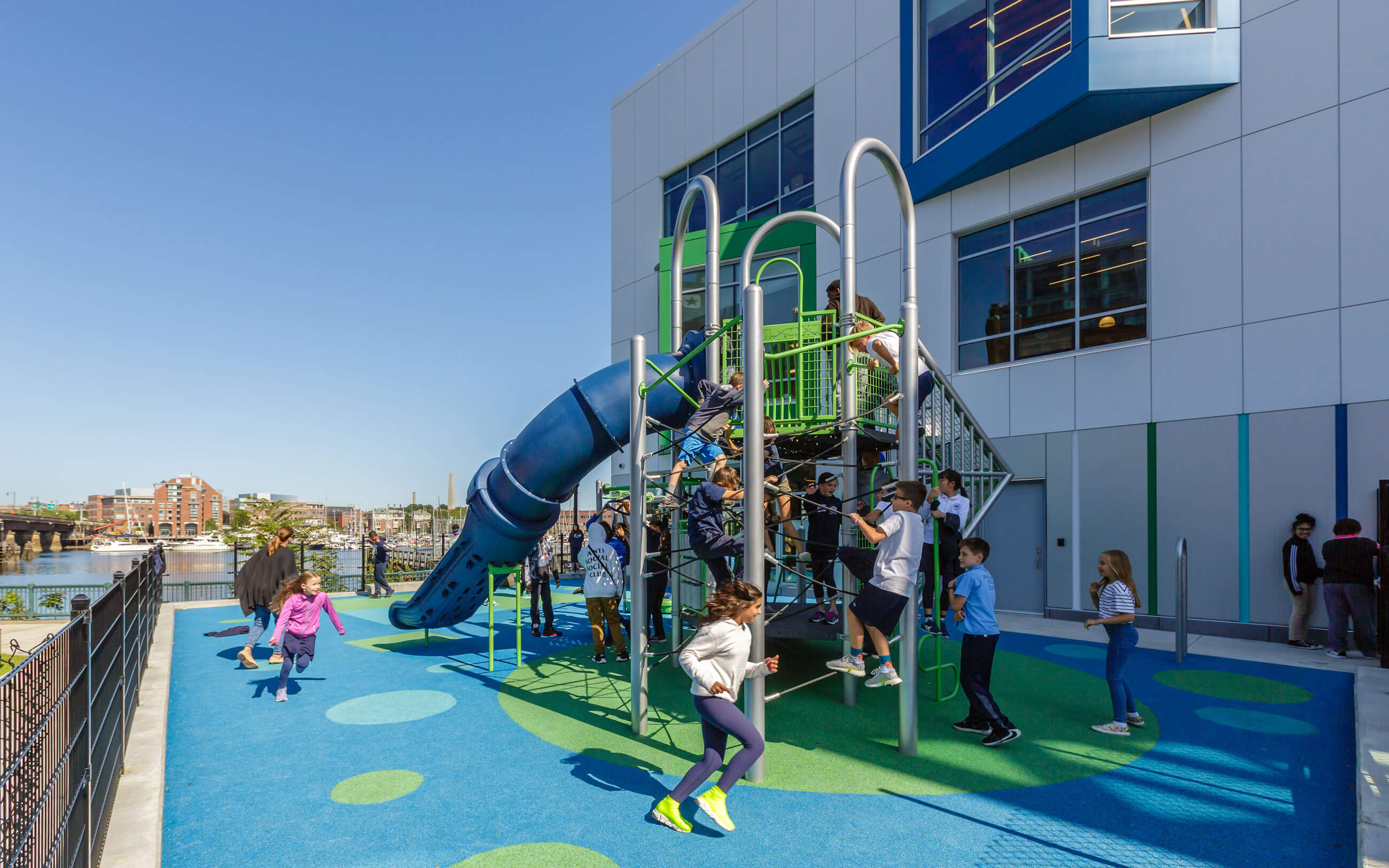 Young students running and climbing on green and blue play structure.