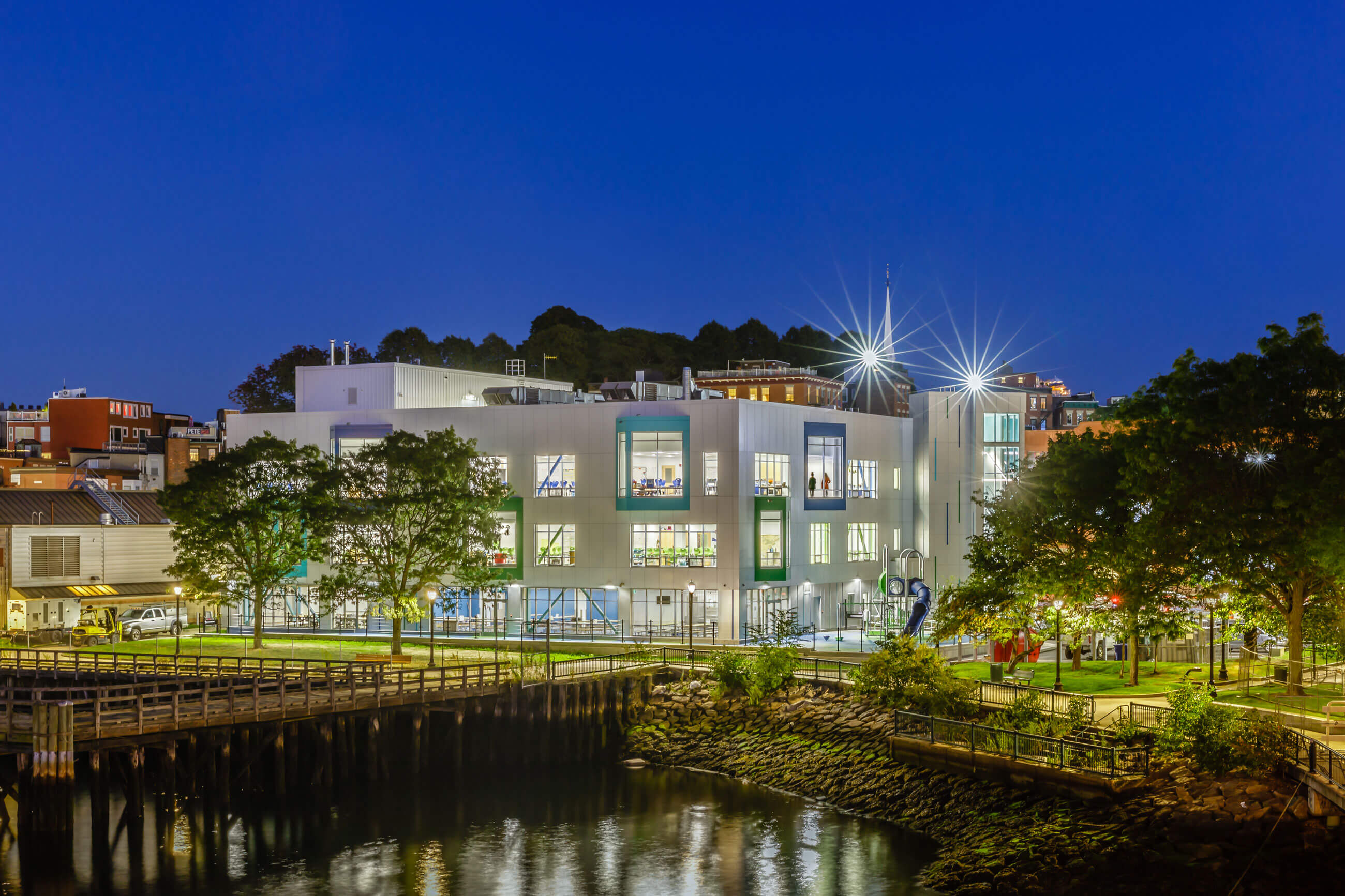 Eliot Innovation school lit up at night, with its lights reflecting on the harbor.