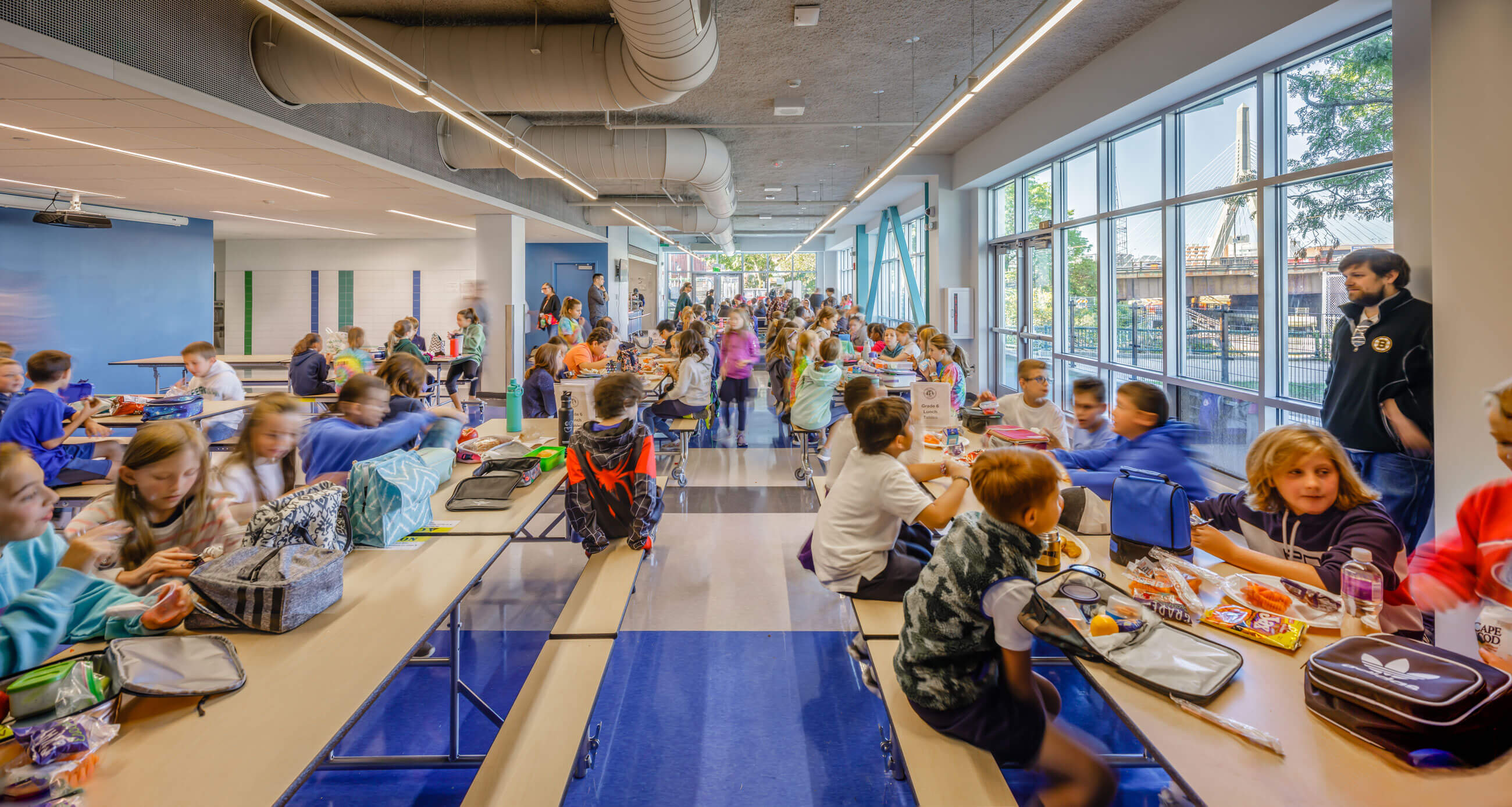 Many kids sitting at long cafeteria tables framed by blue floors, large windows, and exposed mechanical systems on the ceiling.