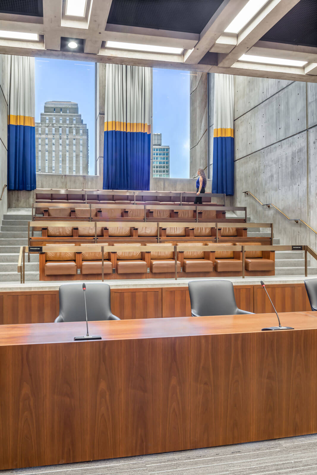 Interior view showing linear desk seating and stadium-step public gallery at the Boston City Hall Council Chambers, renovated by Finegold Alexander Architects