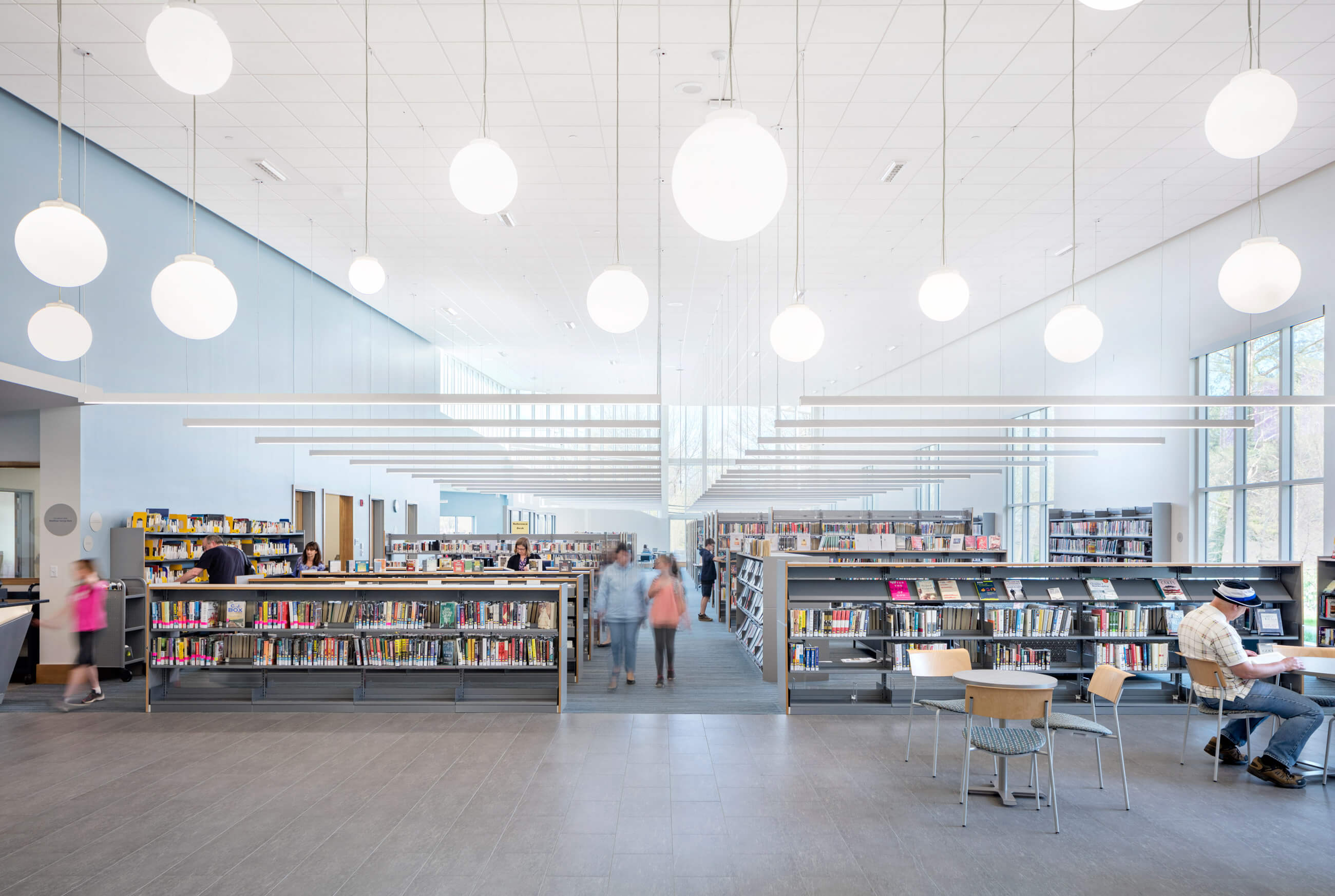 Low library stacks with open space and orb lights hanging from a high ceiling. Light blue walls and white ceiling accentuate natural daylight.