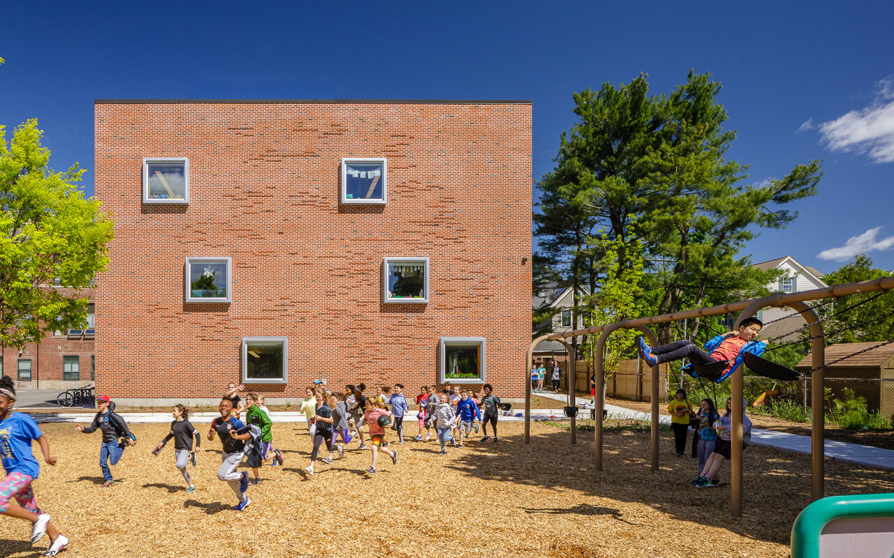 Students running in front brick rectangular structure, with six offset windows and tree pattern formed by extruding bricks.