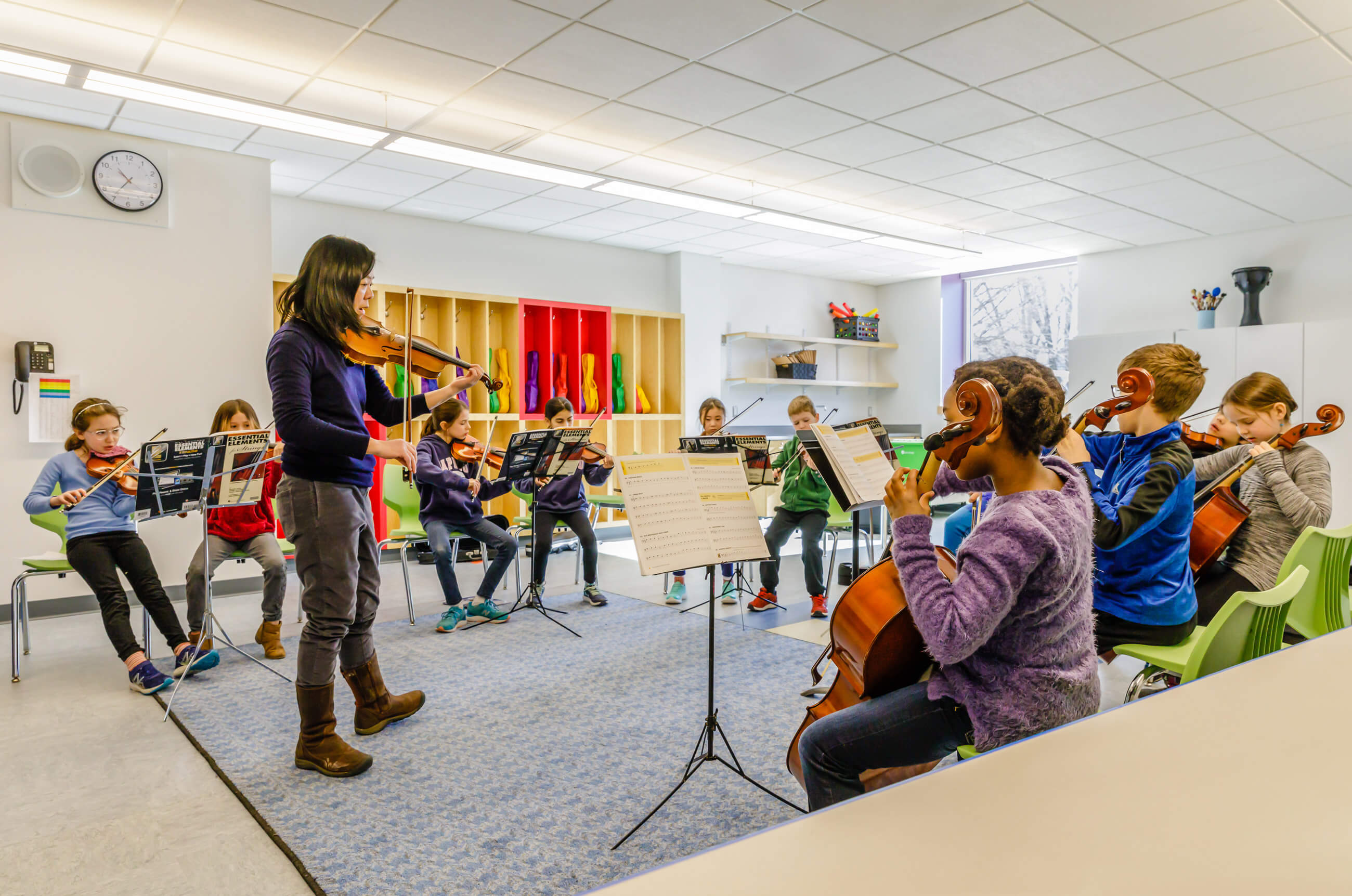 Teacher standing in front of students teaching violin or viola in front of colorful yellow and red cubbies.