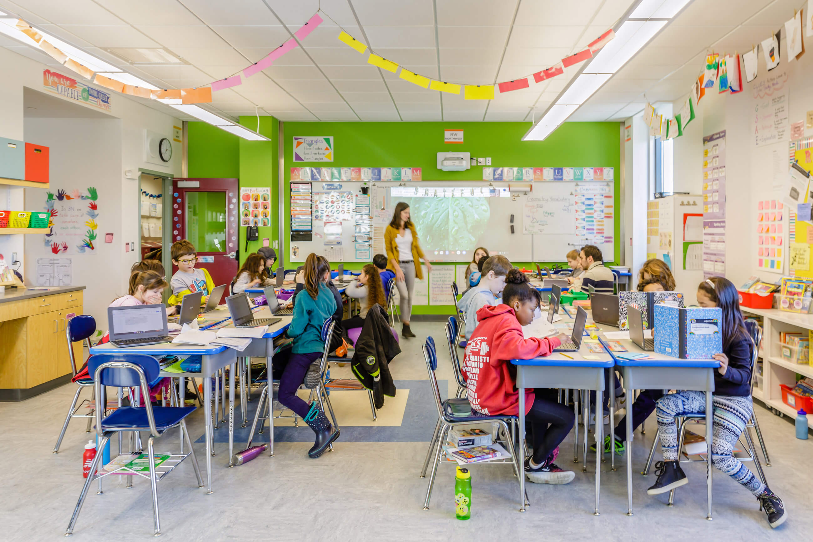 Students at their desks in a classroom with the teacher in front of the whiteboard on the green wall, with streamers hanging from the ceiling.