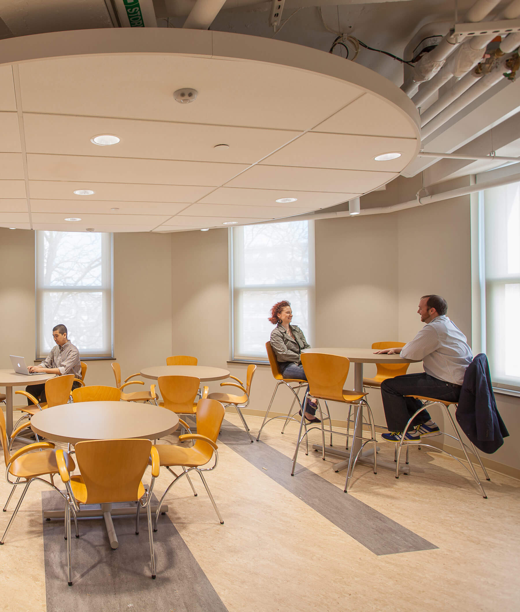 Casual dining space with office colleagues at the Cambridge Housing Authority, showing warm finishes, natural daylight and also exposed MEP systems