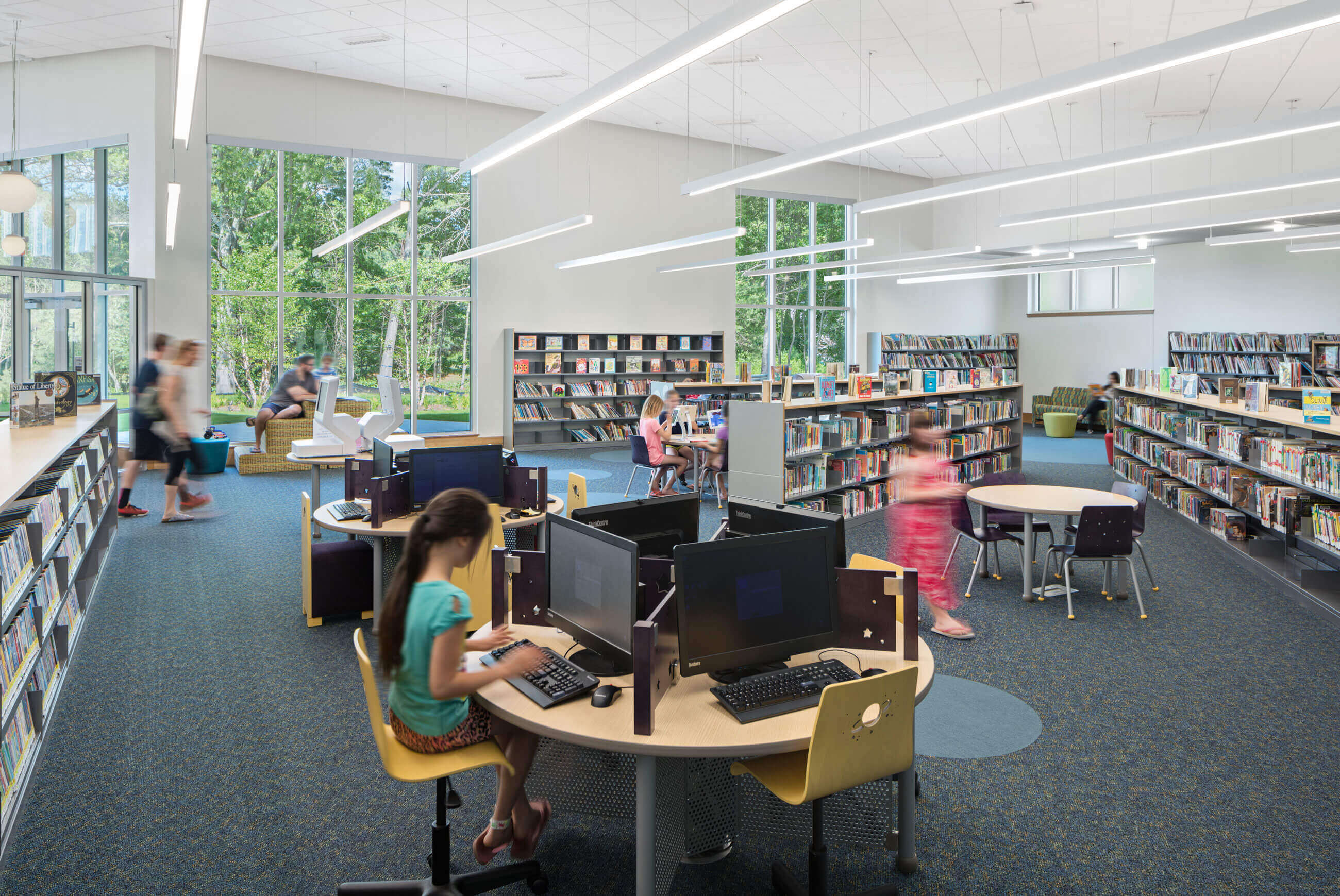 Girl at circular computer table, other children walking around bookshelves and sitting at tables with views onto lush green trees.