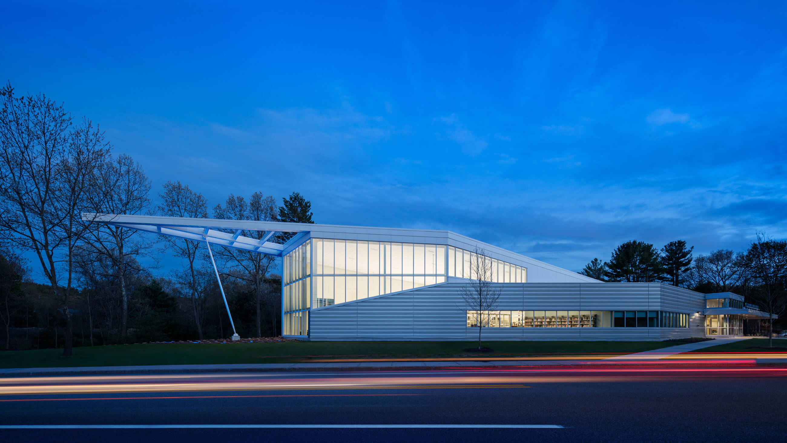 Horizontal view of the library from across the street with overhang protruding glass and light-filled structure