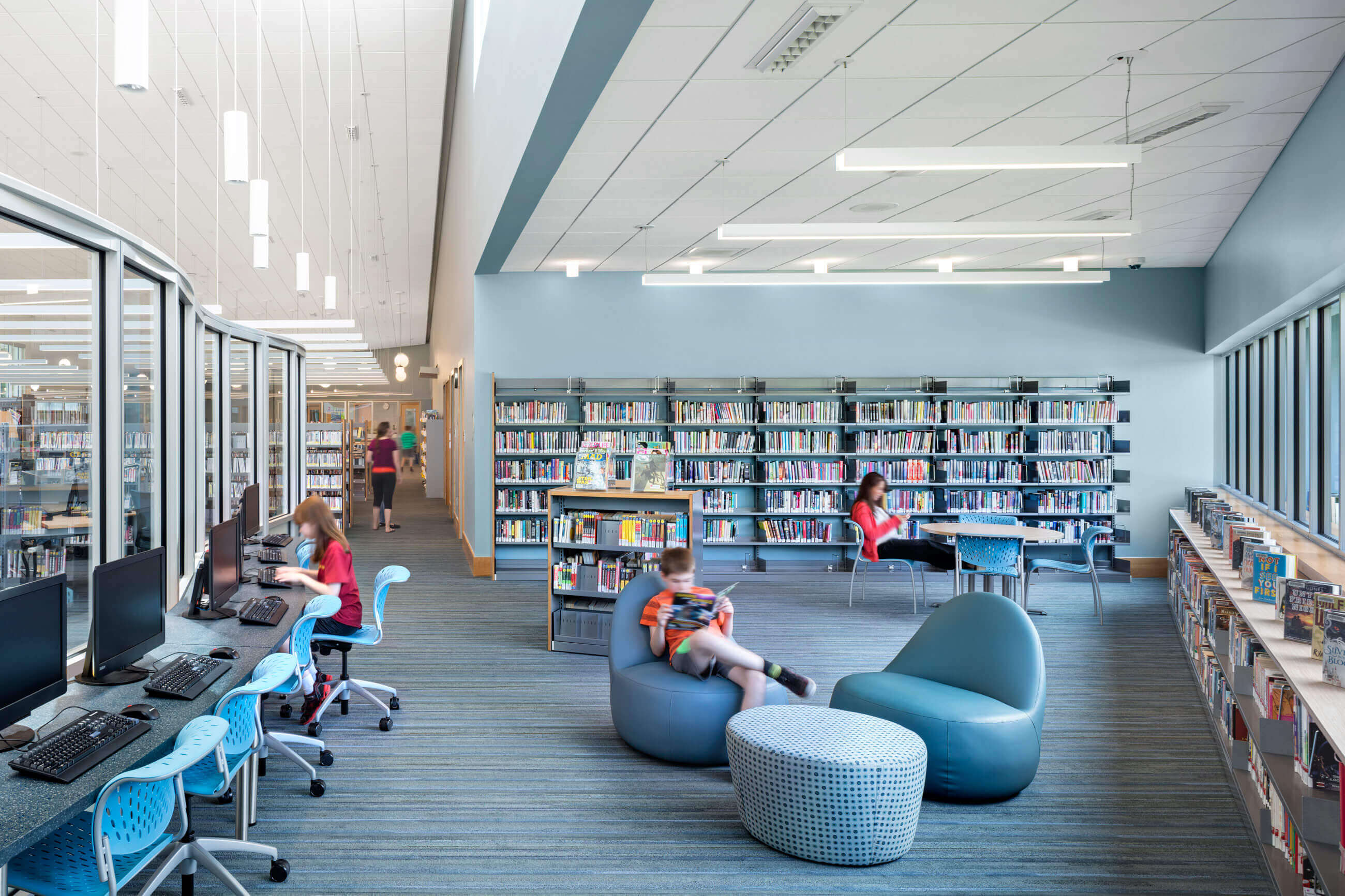 Computers with curvy glass separation, modern blue seating area with bookshelves behind.