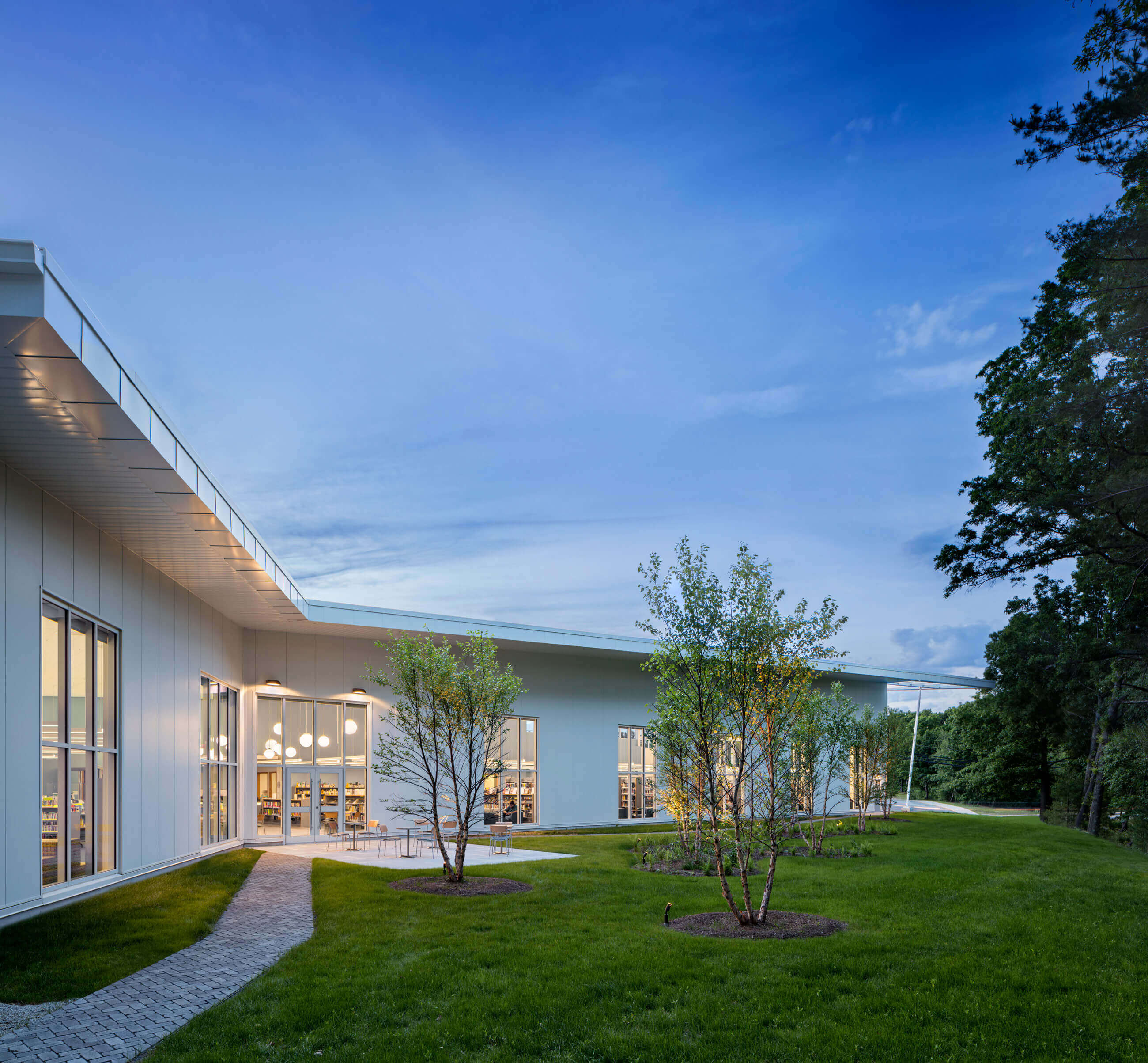 Exterior of the library at dusk, angled around a small courtyard and trees.