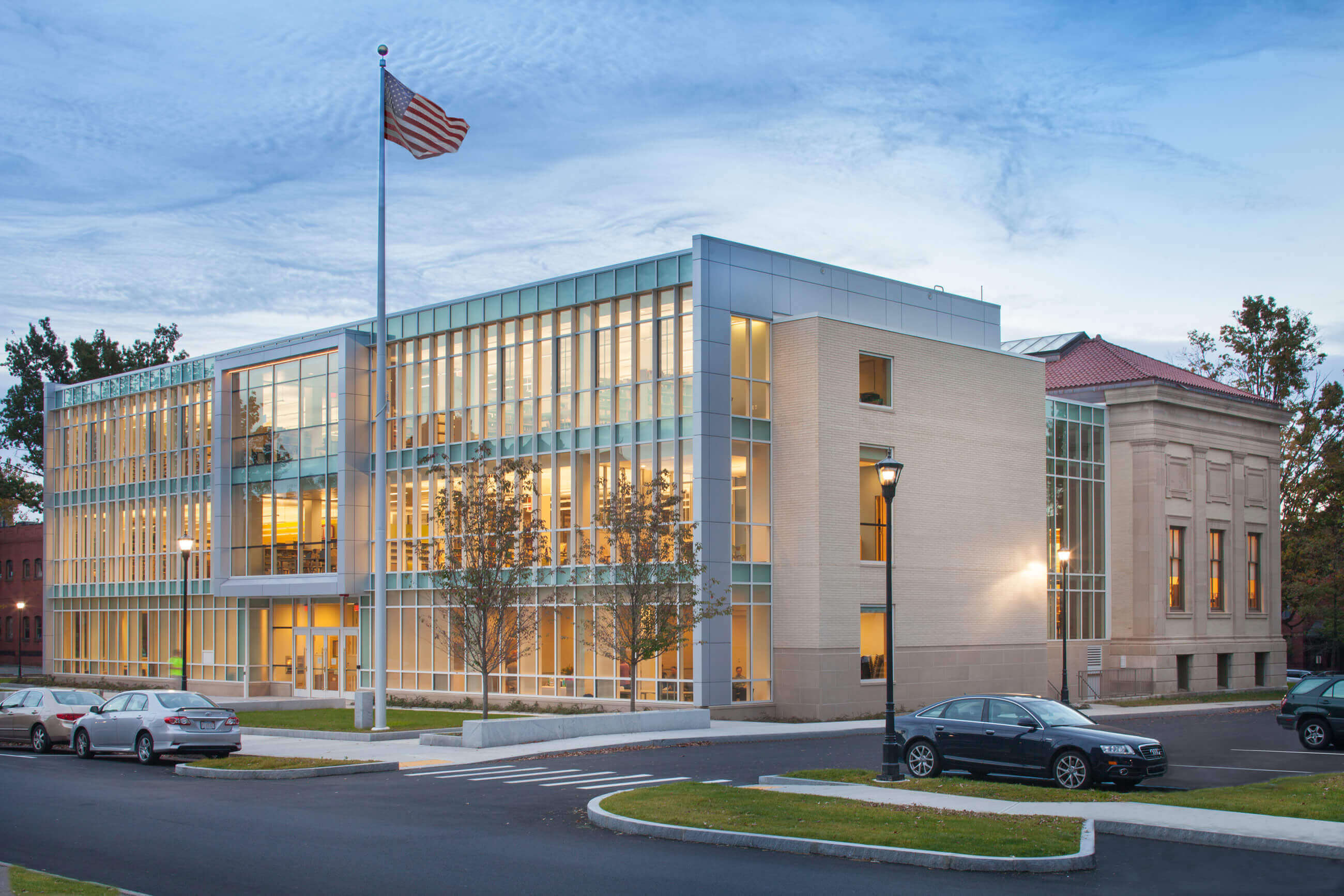 Modern glass and stone addition blends to the historic library in the right of the frame at dusk.