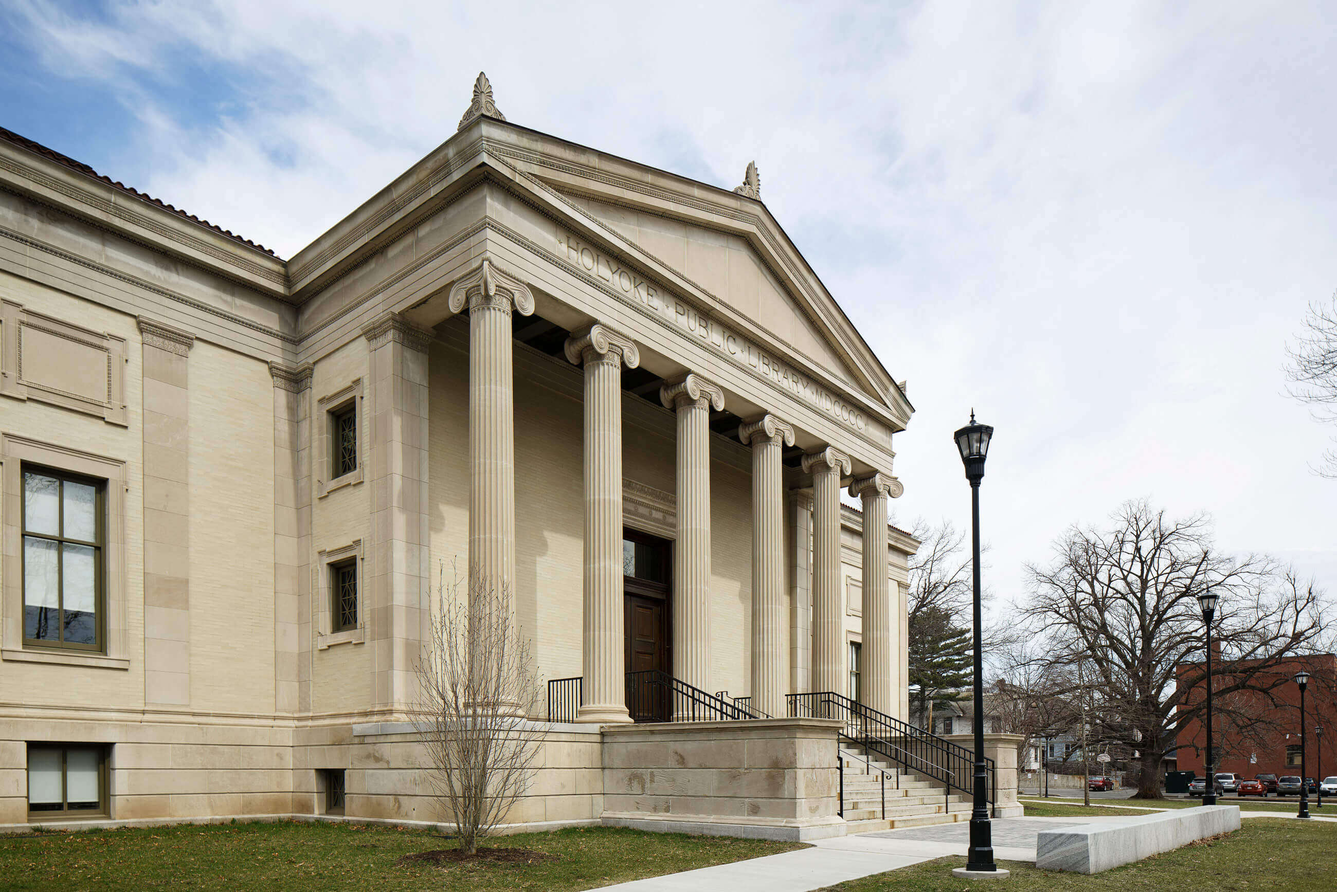 Angled view of the historic Greek Revival facade of the Holyoke Public Library.