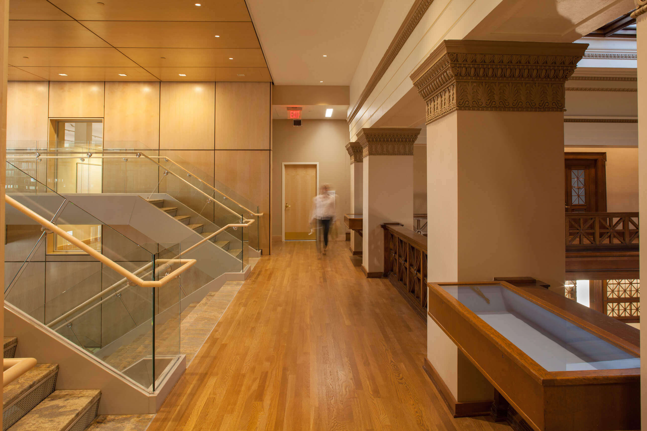 The sleek wooden and glass stairway connects the existing library building with the new addition.