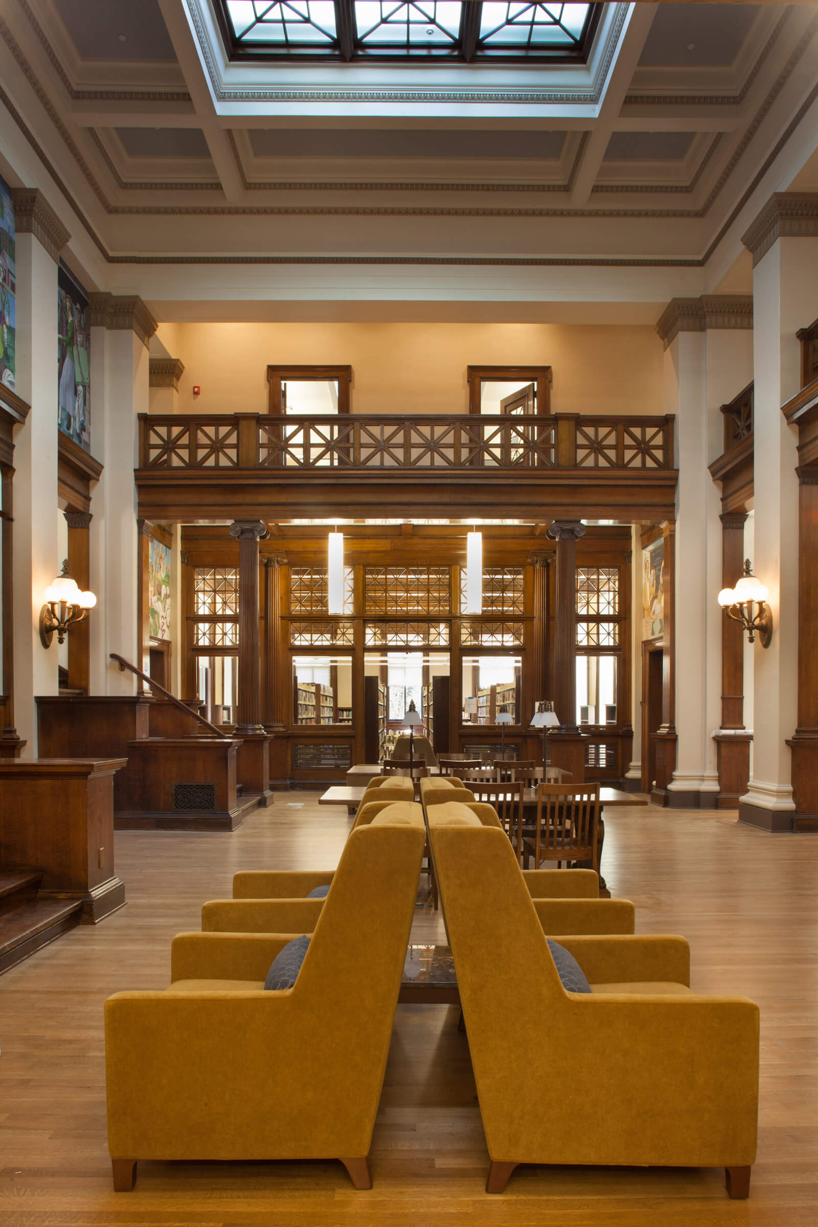 Historic double-height atrium of the Holyoke Public Library with yellow seating in the foreground and carrels in the background.