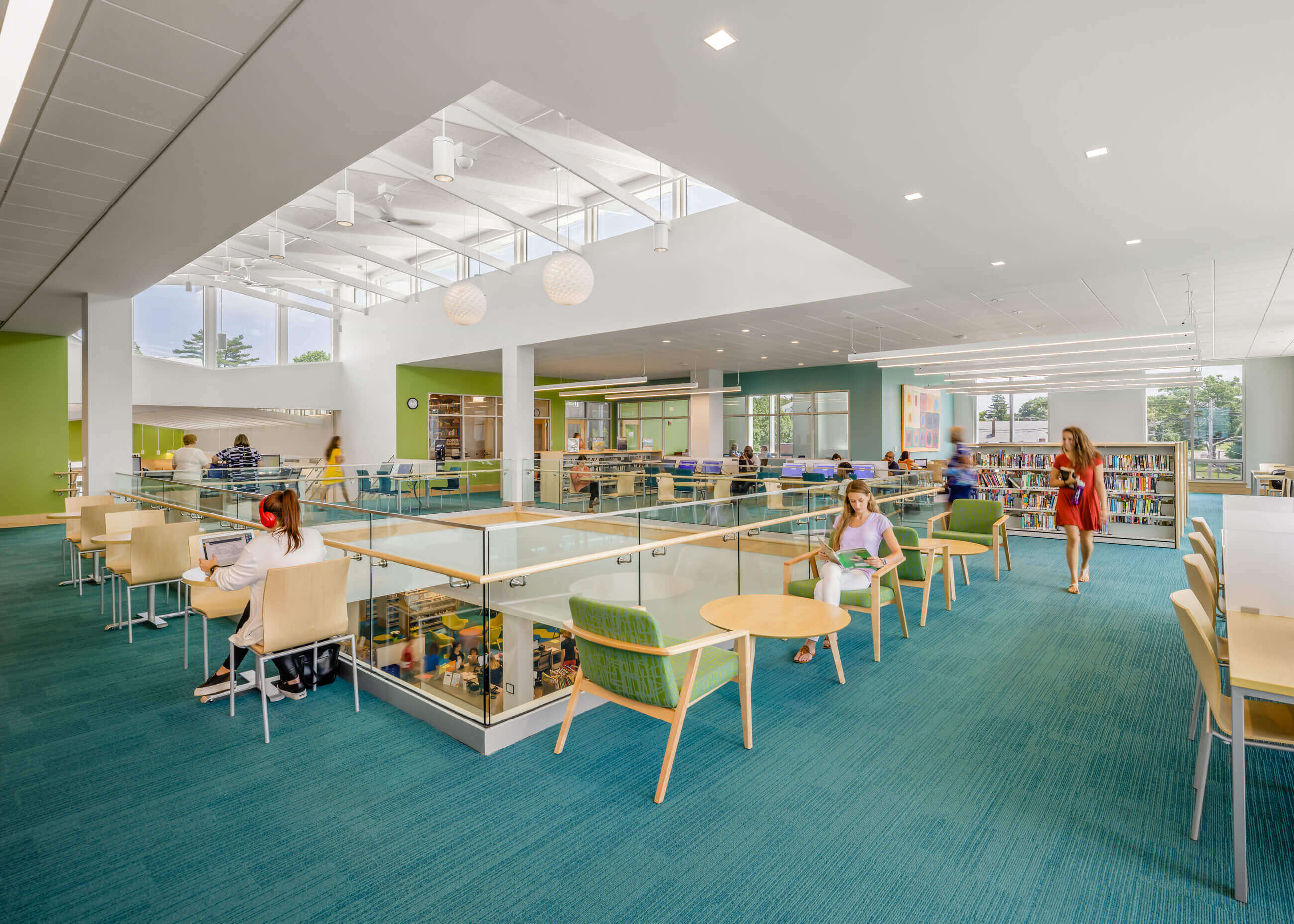 Library patrons in comfortable chairs in a bright, naturally lit space with green and teal colors, overlooking the floor below.