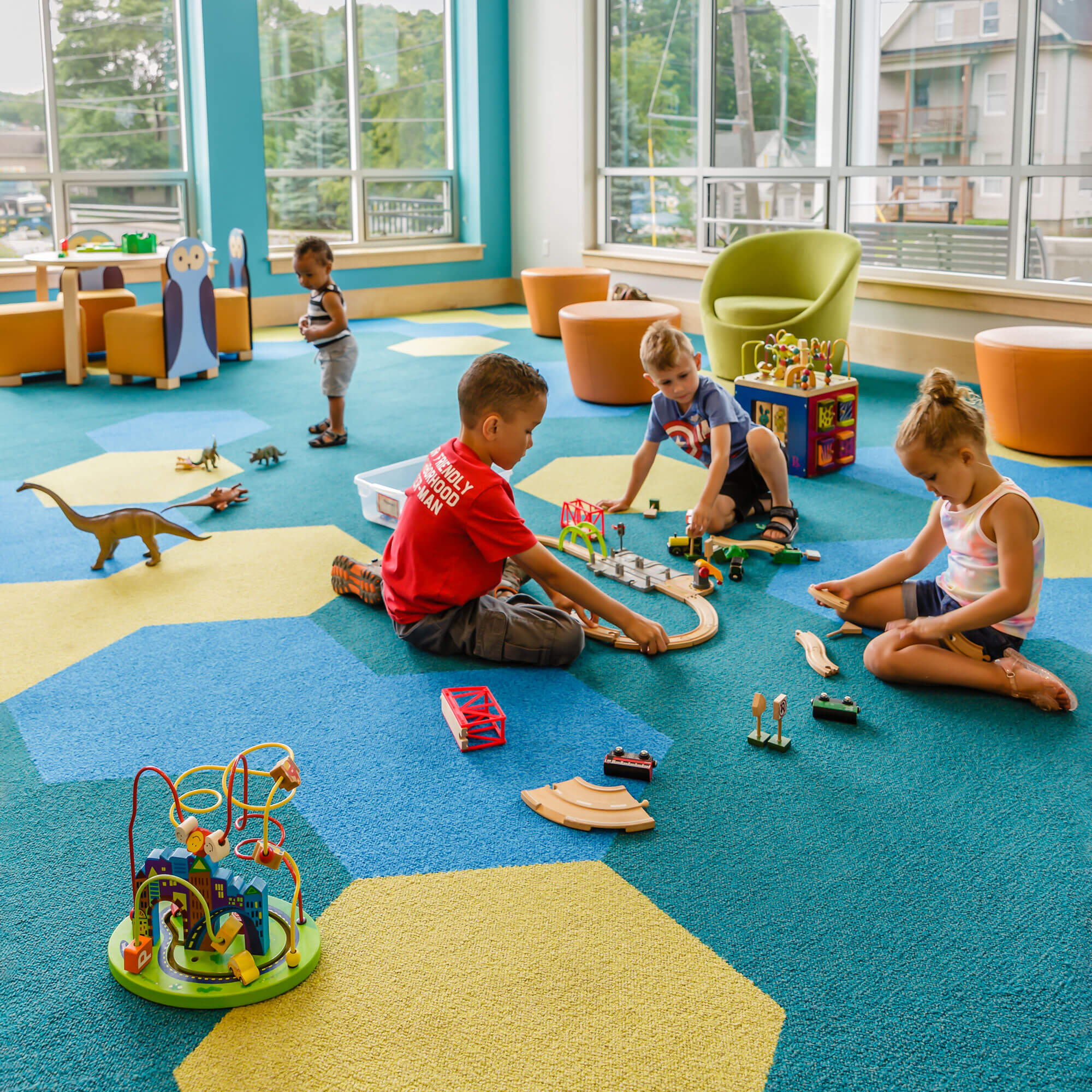 Children playing with toys on a green, blue, and teal carpet with green chairs and orange tables in the background.