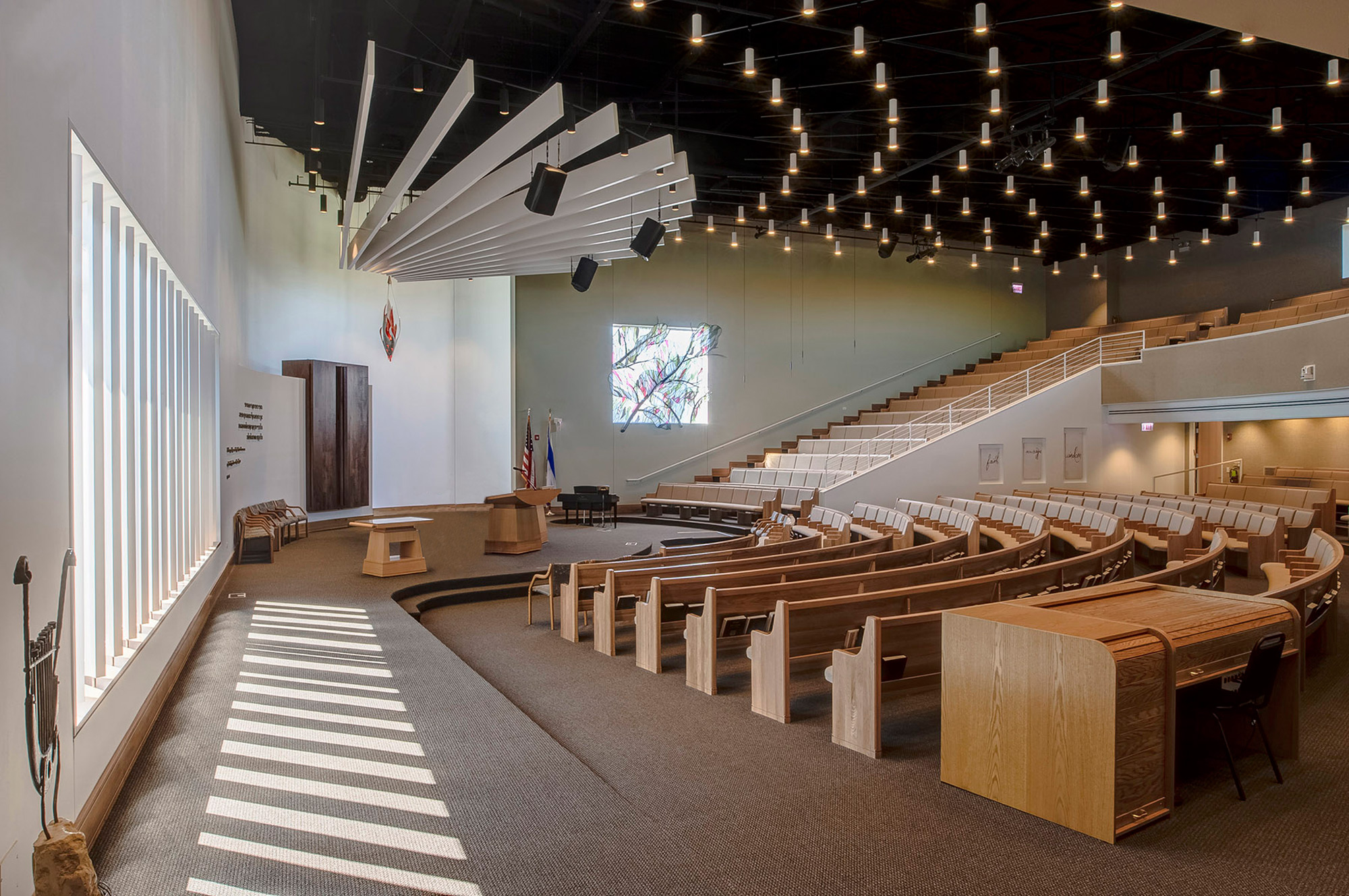 Synagogue sanctuary with different kinds of seating areas, ceiling lights, and the eternal flame