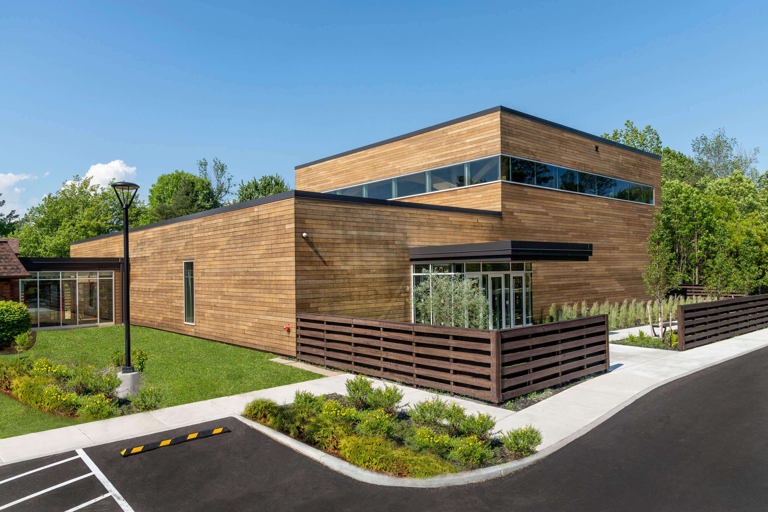 Exterior of the new portion of Temple Beth Tzedeck, wrapped in wood with a glass entrance and long ribbon-like windows.