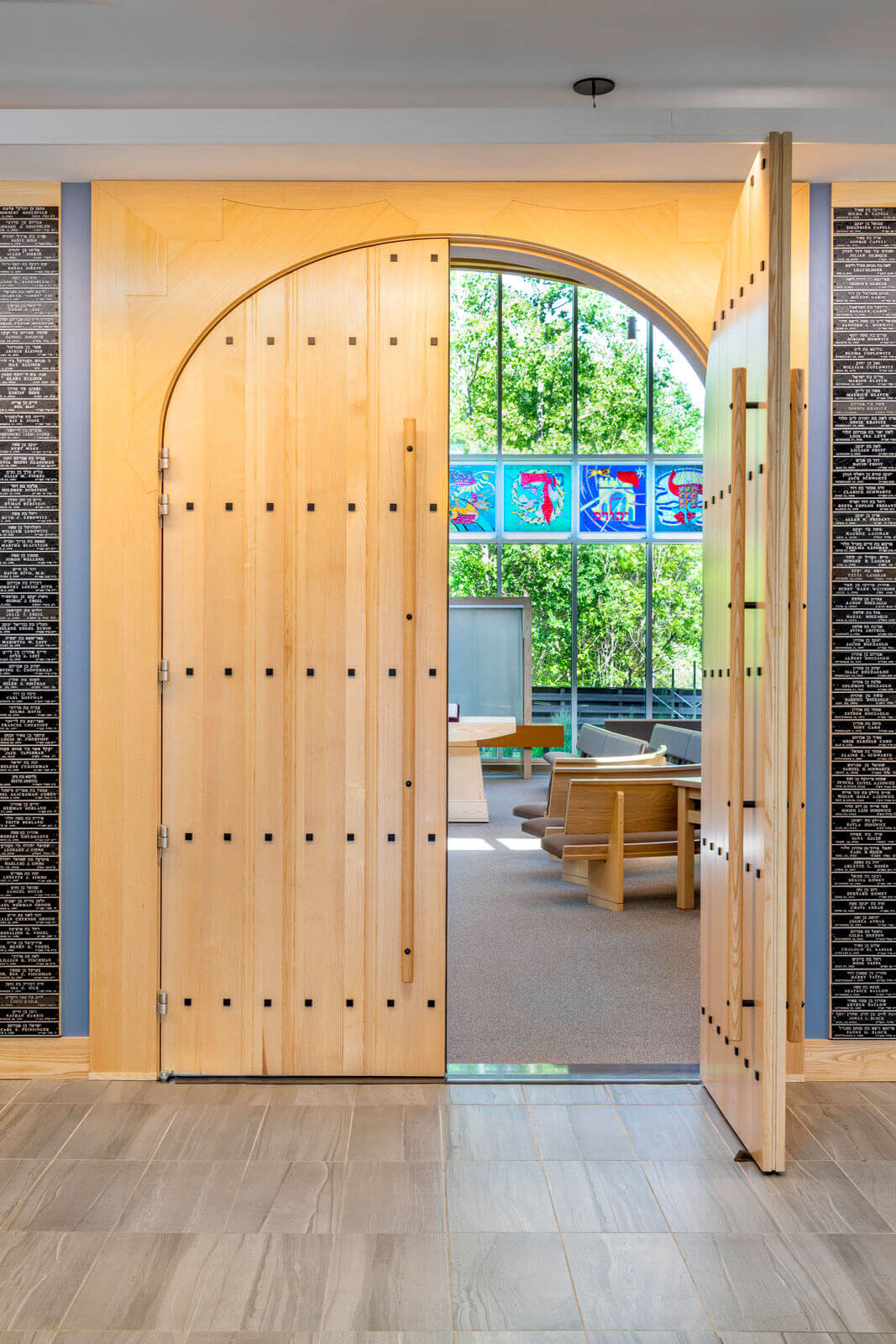 Wooden arched door opening to the sanctuary inside, revealing a bright, sunlit space with views to the woodlands surrounding the Temple.