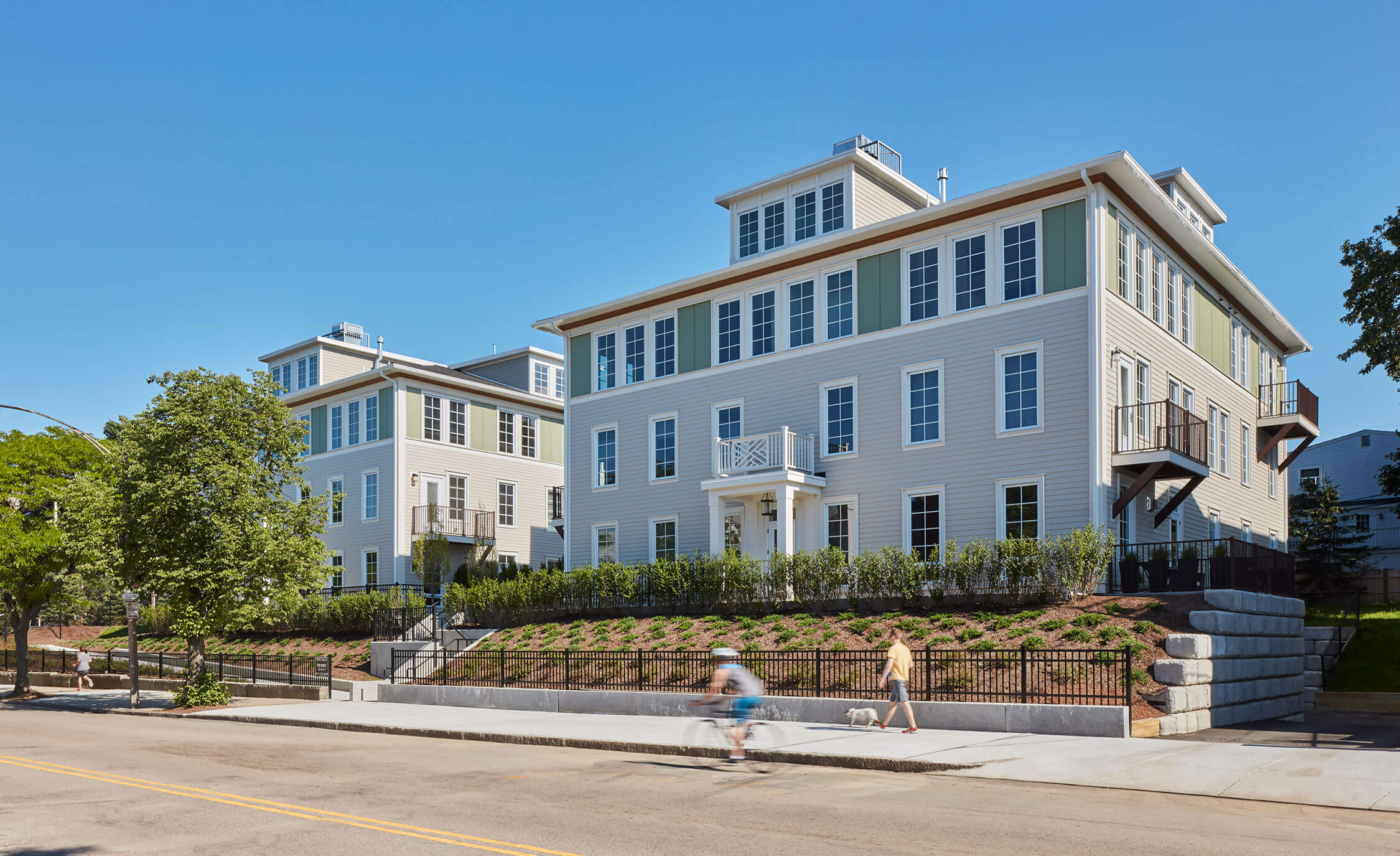 View across the street of 945 East Broadway Street, two large buildings with a wooden, residential feel.