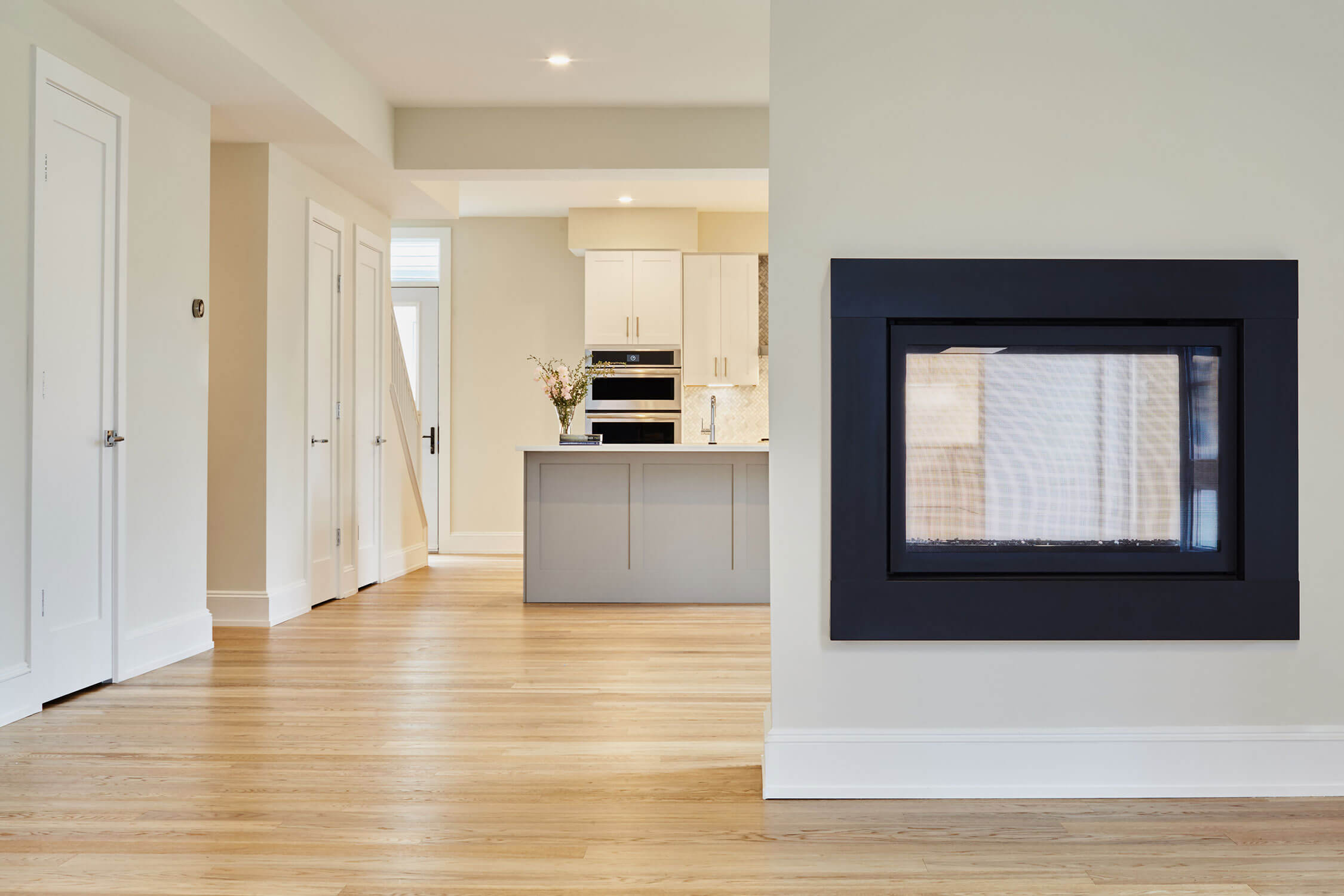 See-through fireplace with view of kitchen island in the background, with wooden floors.