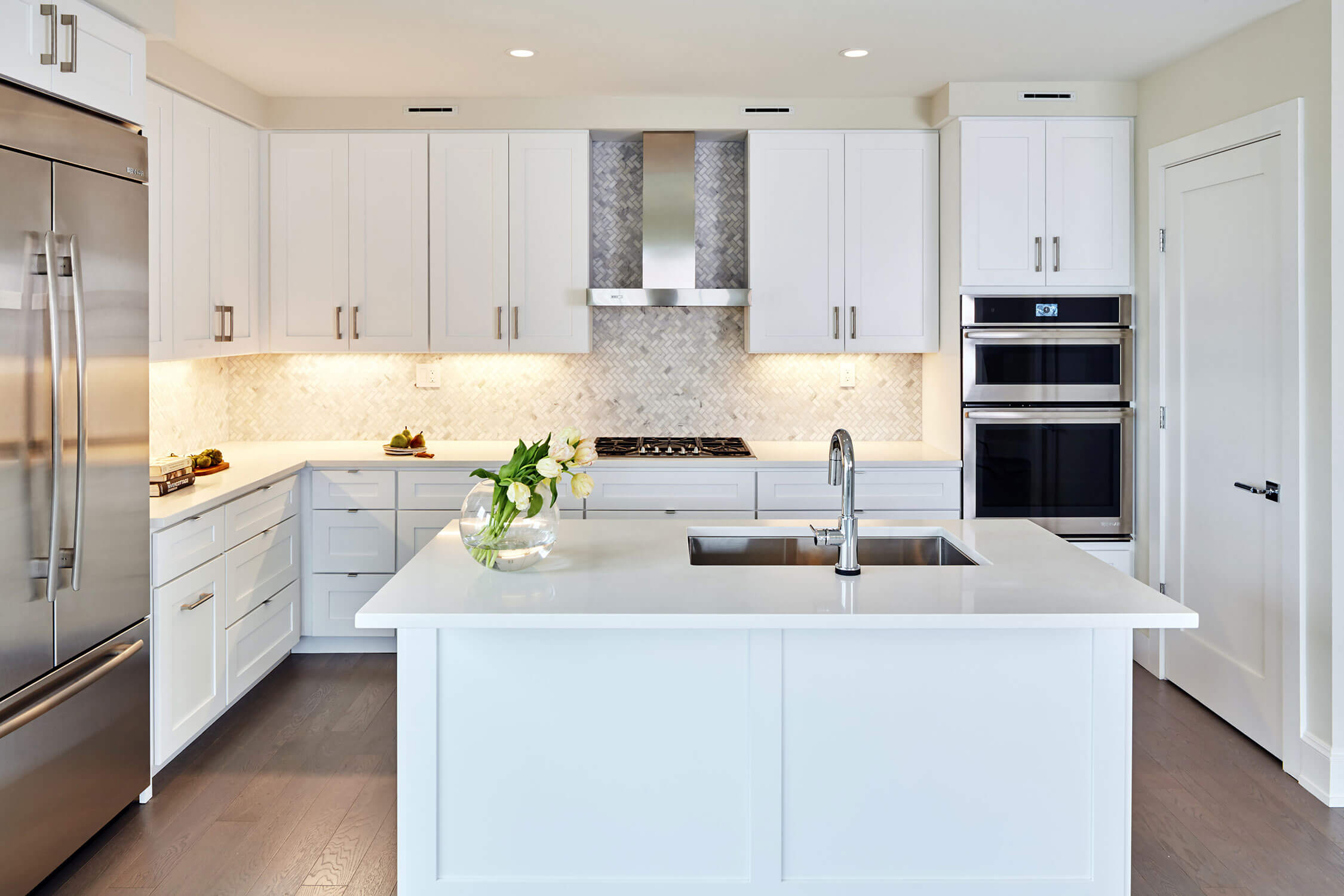 Modern kitchen with a fridge on the right, and a white island with a sink and flowers on it.