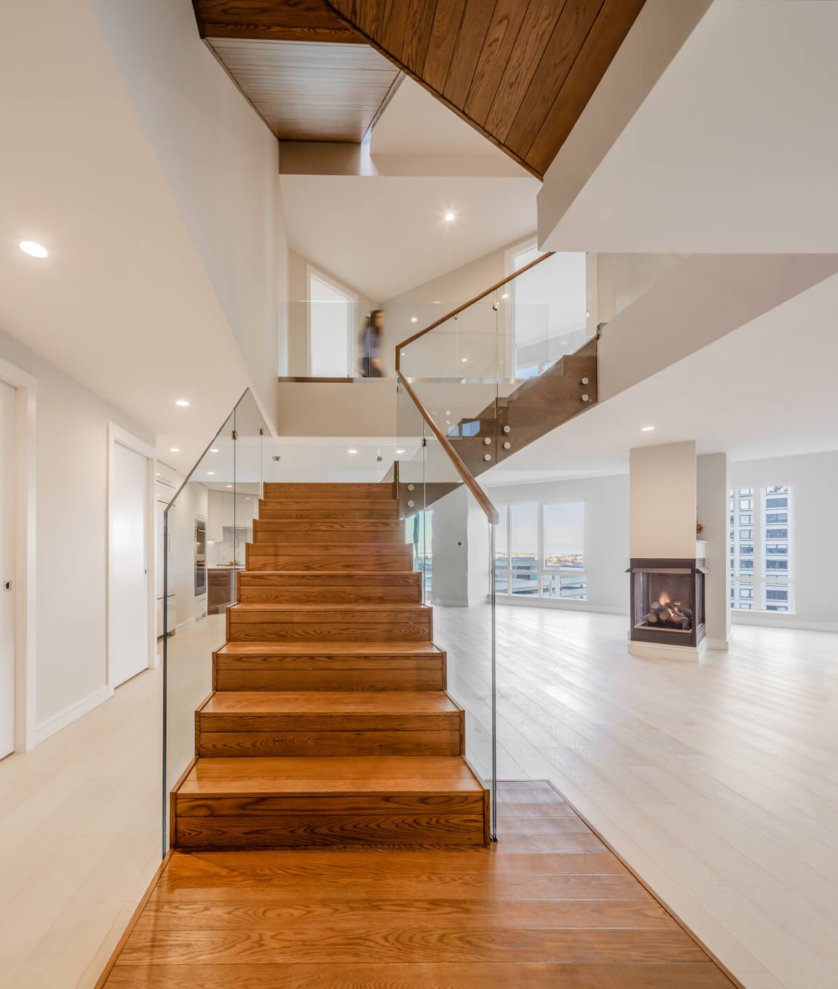 Angled wood and glass staircase in a white, empty apartment unit.