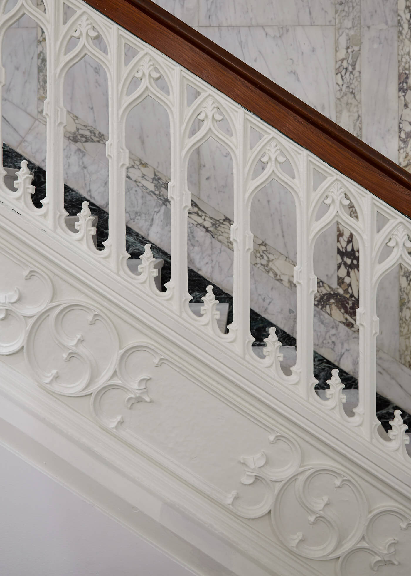 Detail shot of carved white and wood railing, with a marbled background.