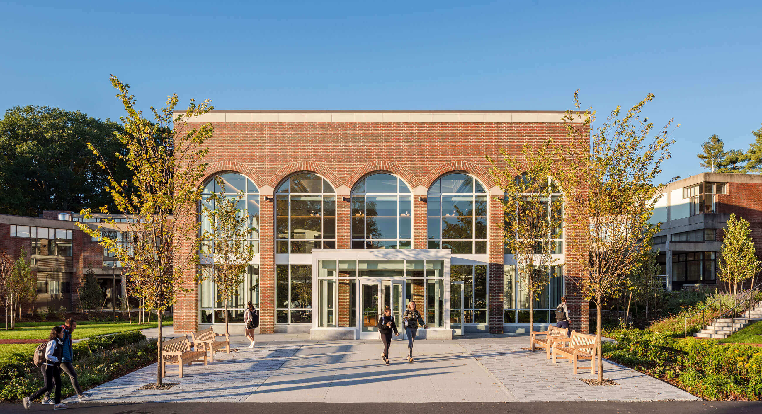 Two college students walking out of the front entrance to the Commons at Babson's Horn Library, a brick rectangular prism with tall arched windows.