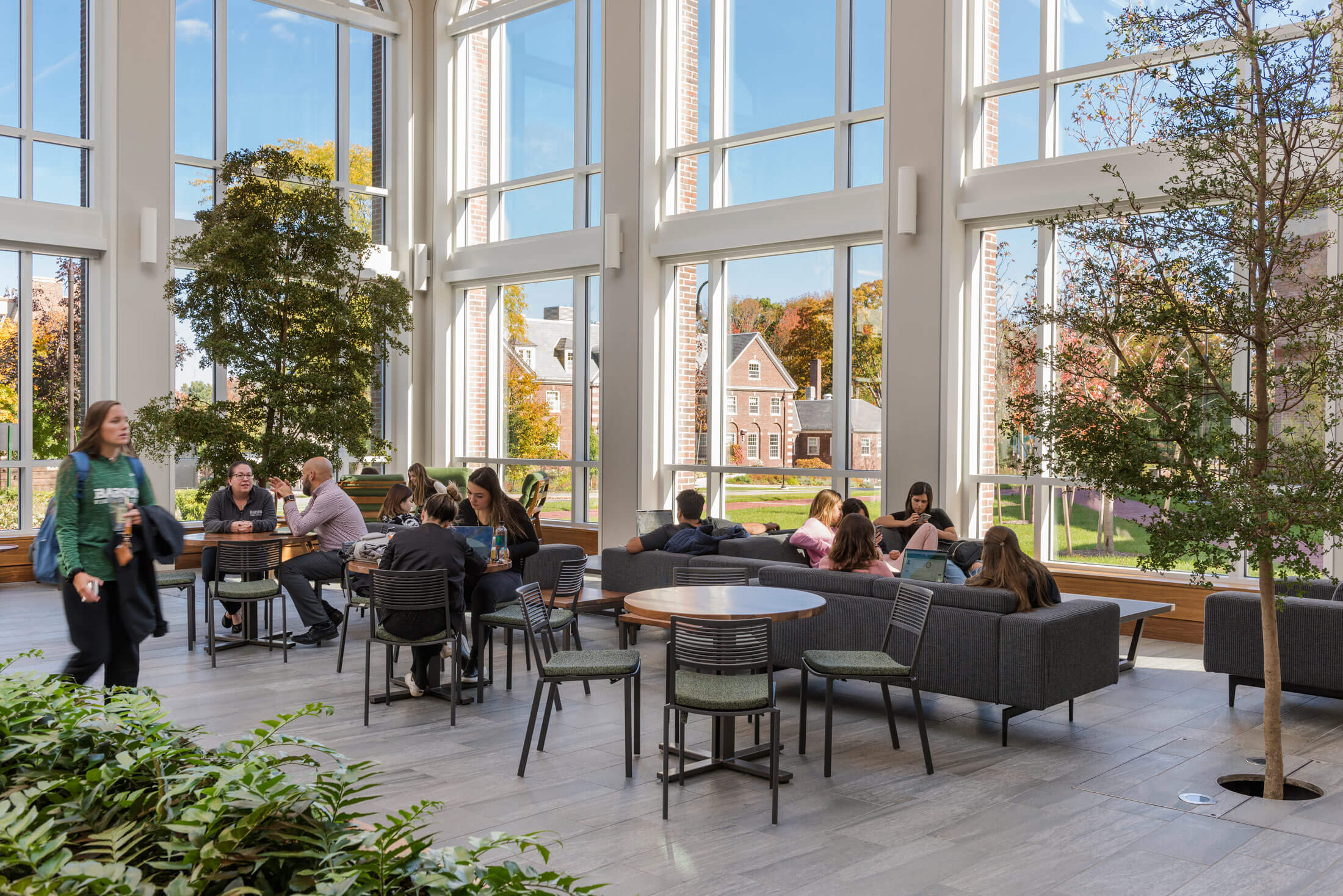 Girl walking by a group of students sitting in couches and at tables in front of tall windows looking out to the campus, with two indoor trees framing the seating area.