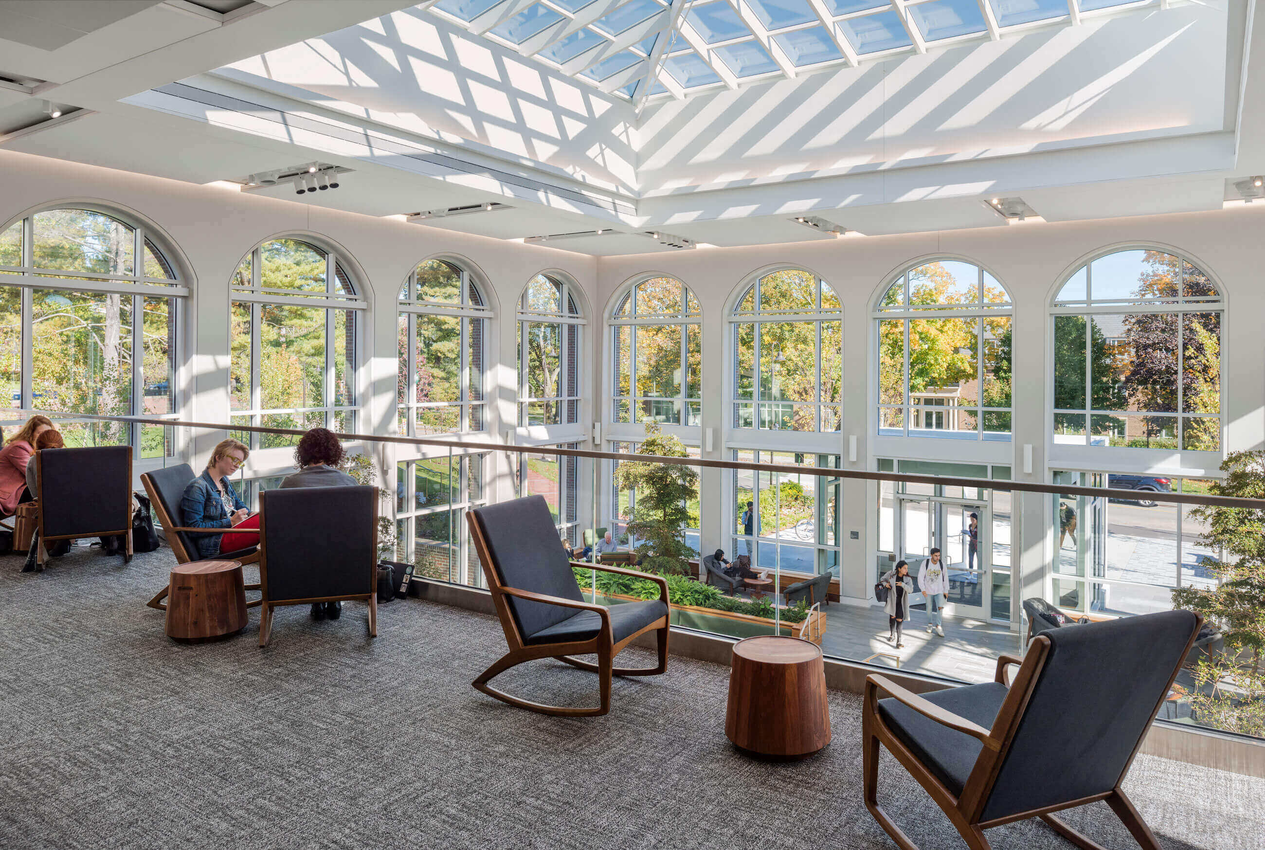 Students in rocking chairs on the balcony of the Commons, with a clear view of the space below, the large arched windows and the skylight.