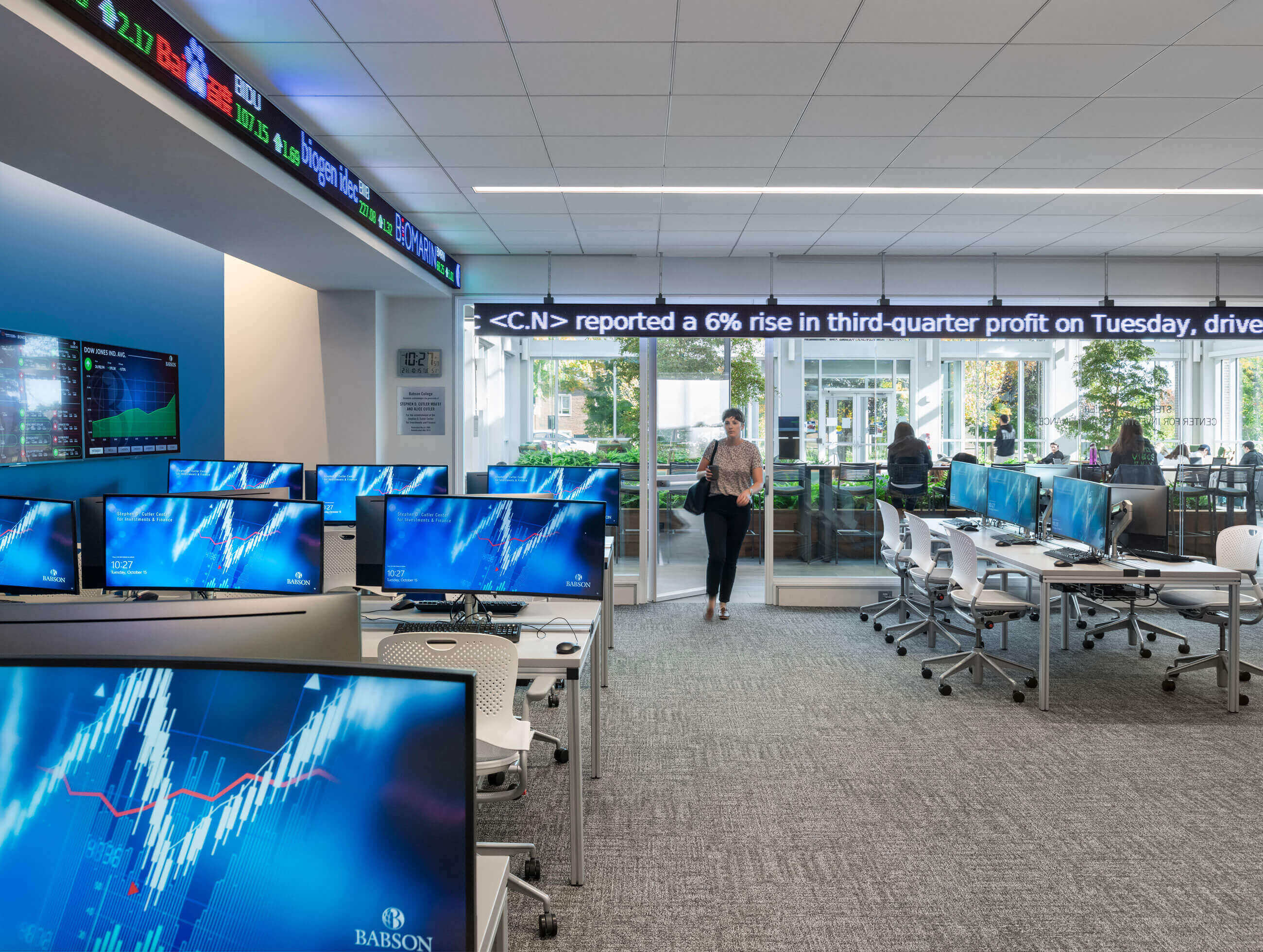 Woman walking into the Cutler Center for Investments and Finance, with blue computer screens to the left and a stock market band across the top of the room.
