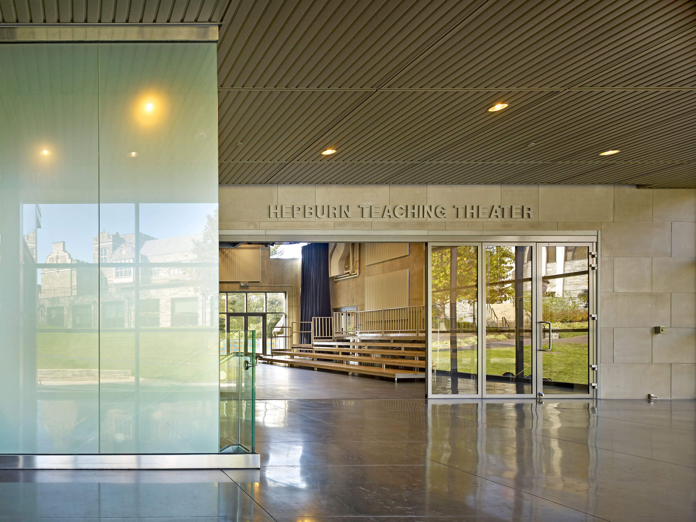 Glass entrance to the Hepburn Teaching Theatre, with natural light reflecting of the polished floor and frosted glass.